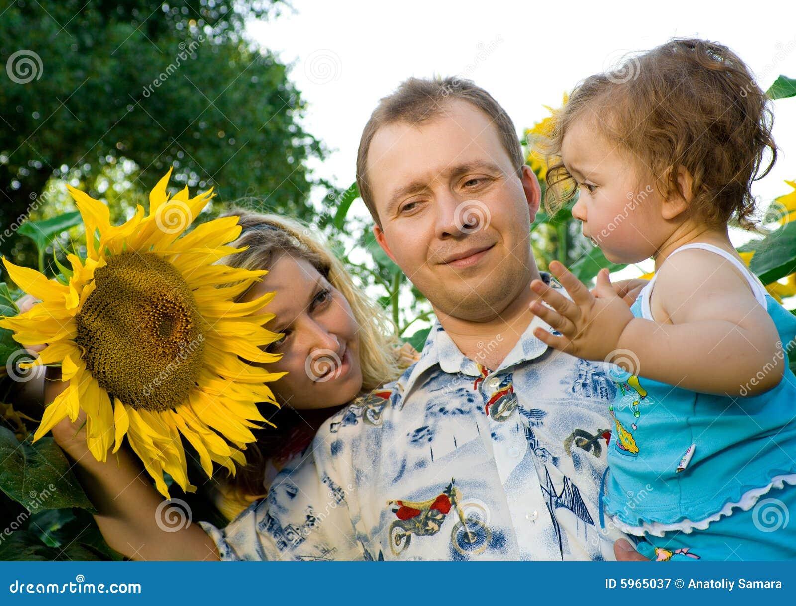 La mamma, il papà ed il bambino in girasole sistemano