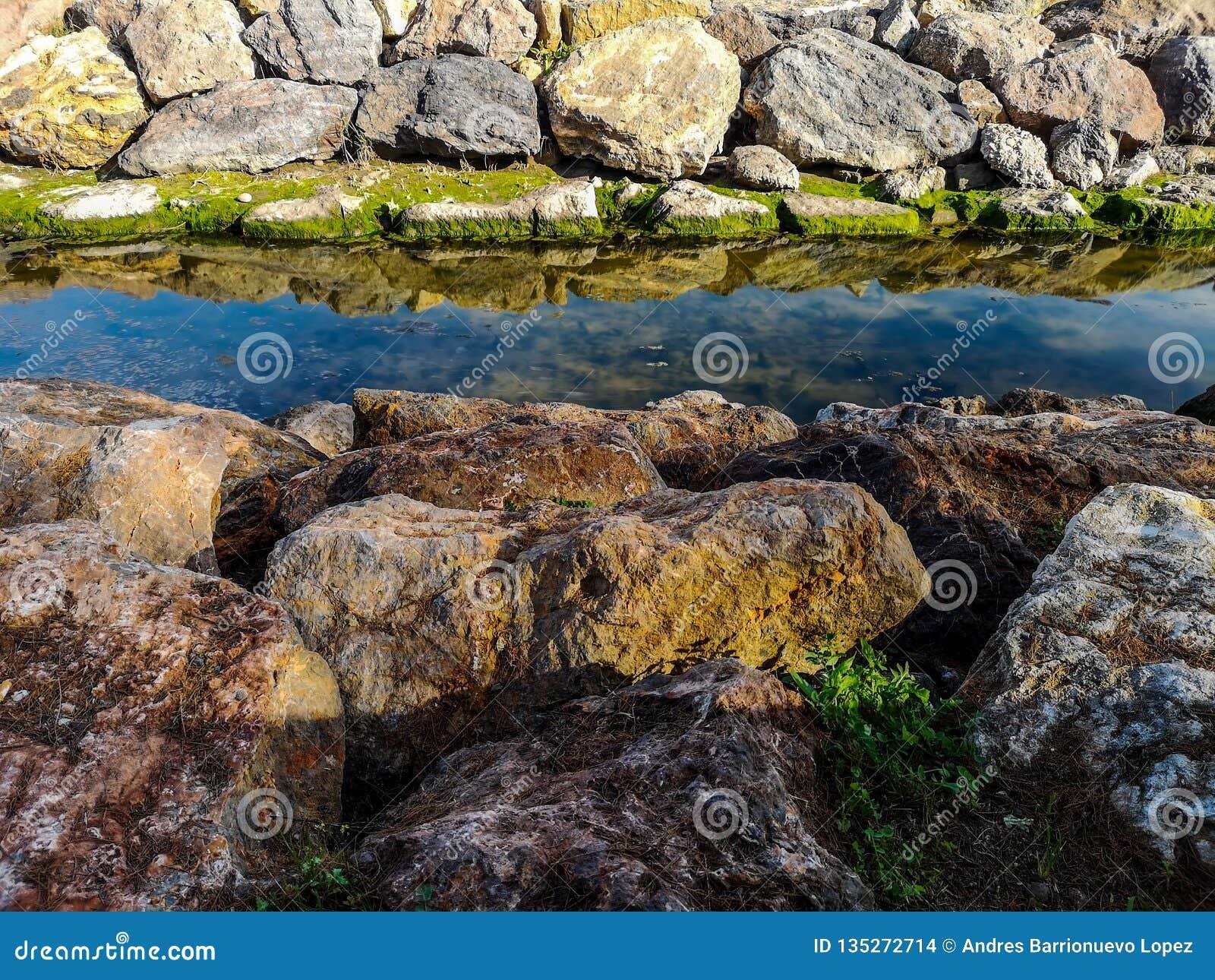 La Manche avec des roches sur les deux côtés et réflexions dans l eau