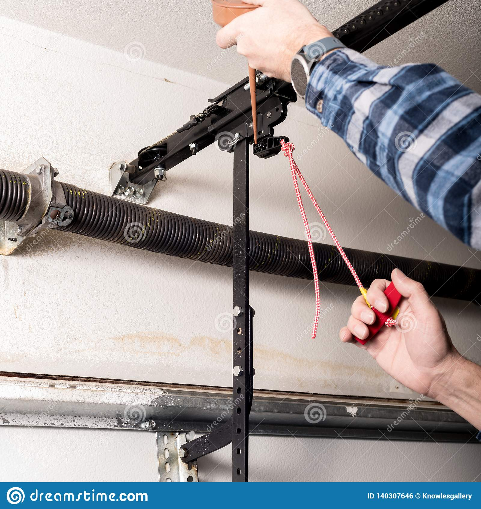 La manitas lubrica a un licenciado del lanzamiento del abrelatas de la puerta del garaje con una poder de aceite
