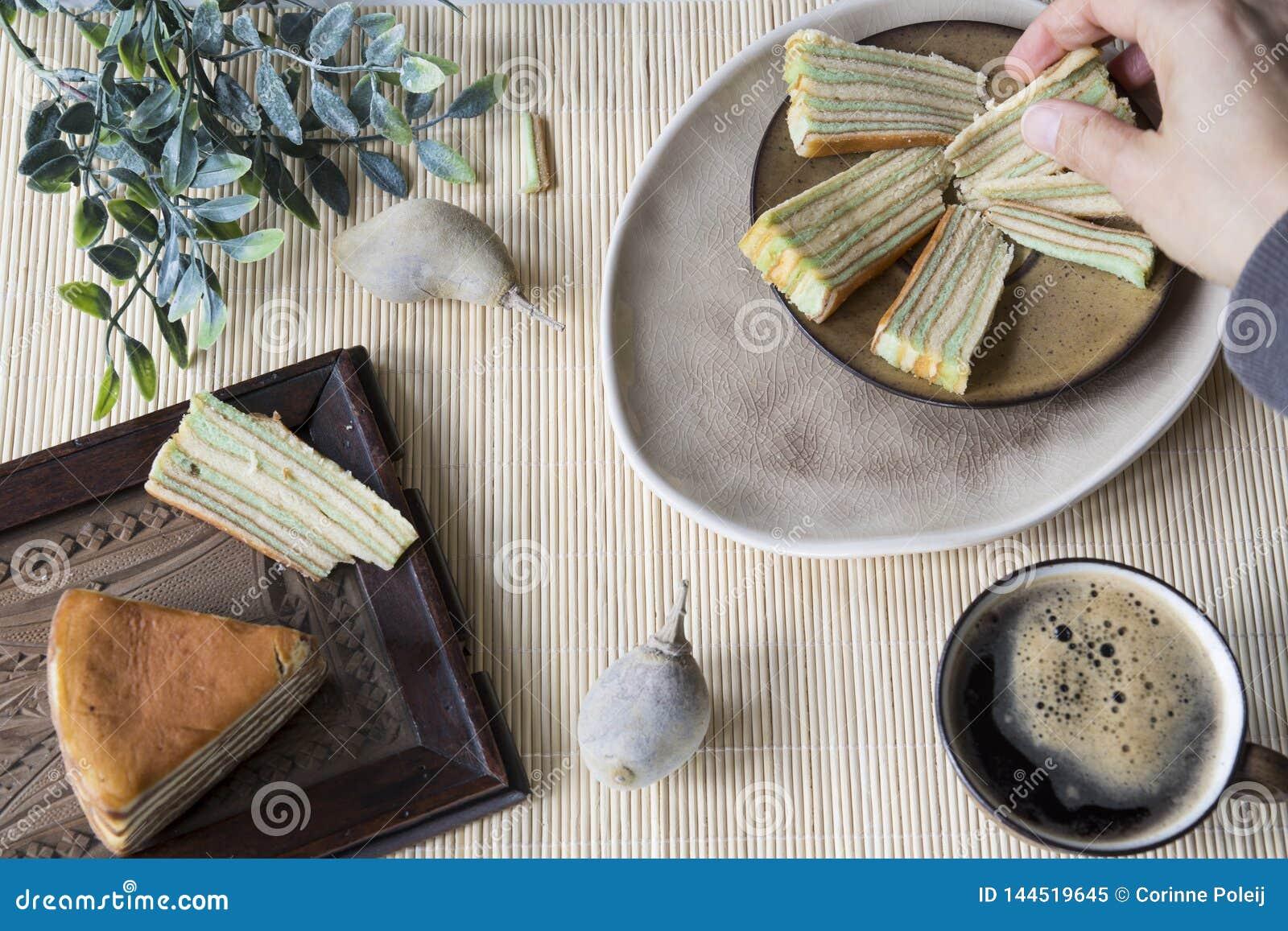 """La mano afferra la fetta di dolce a più strati chiamata """"legit di lapislazzuli """"o """"spekkoek """"dall Indonesia"""