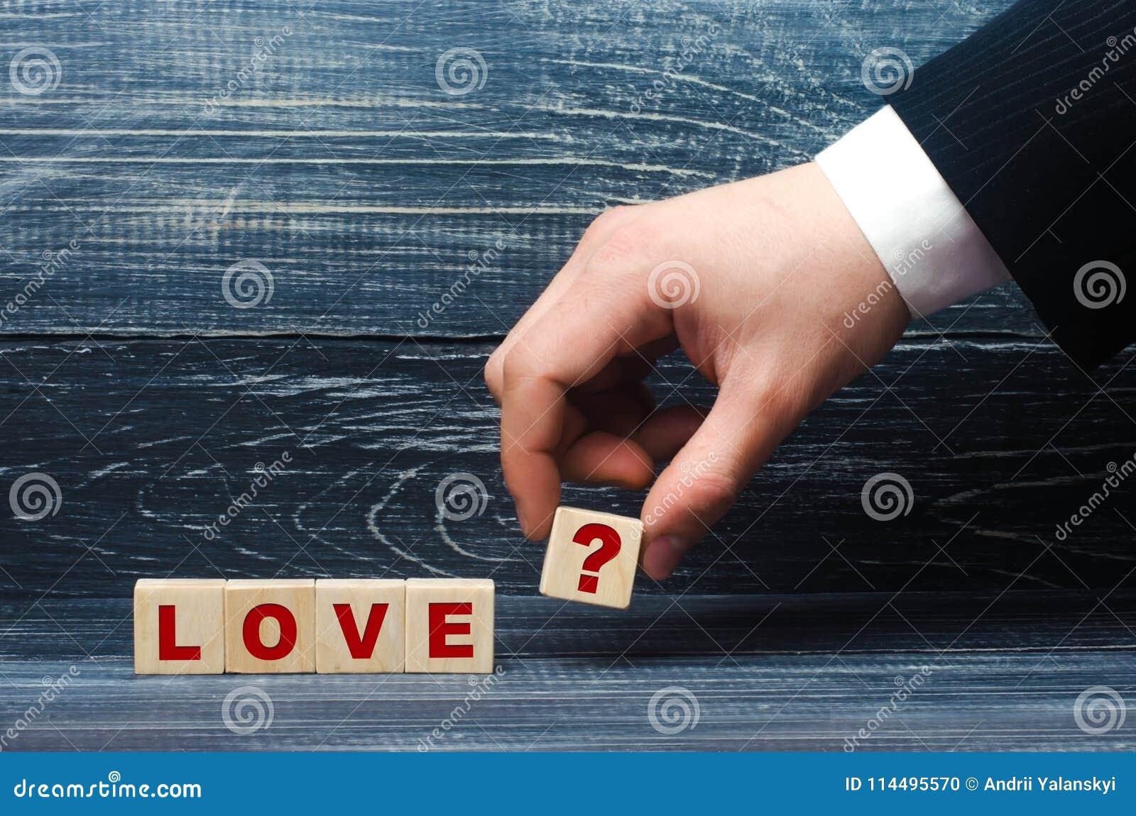 La mano allunga un cubo con il simbolo del punto interrogativo all amore di parola Il concetto di amore e delle relazioni di amor