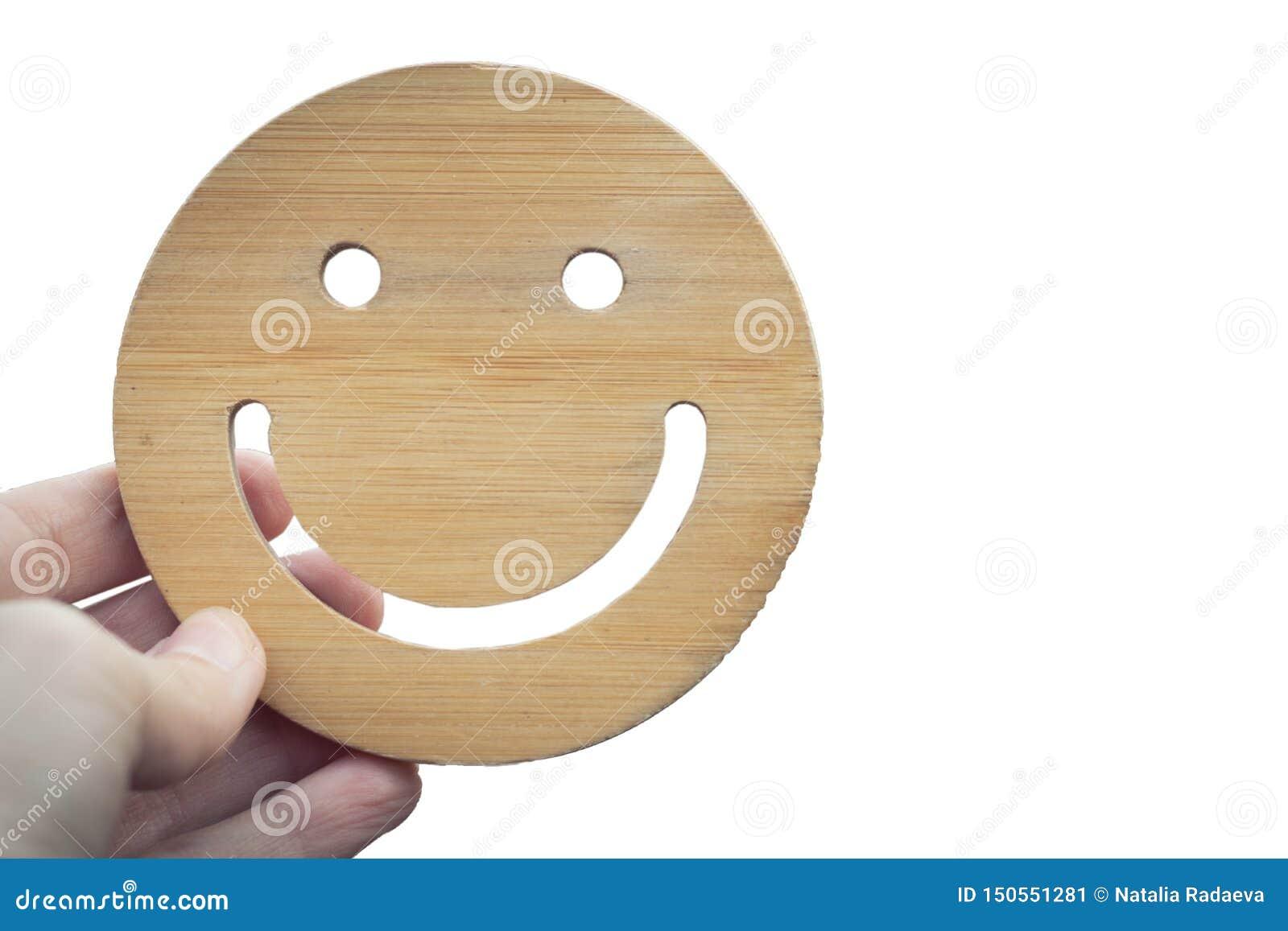 La mano celebra sonrisa redonda de madera en el fondo aislado blanco Mano que sostiene la cara sonriente ning?n cuerpo Emoji, la