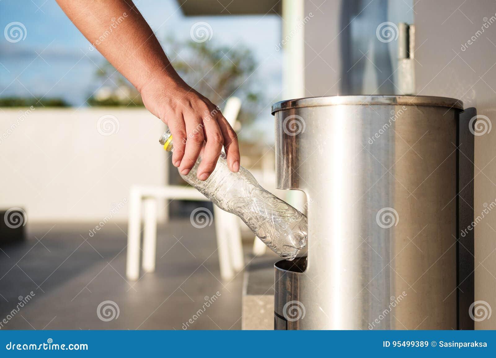 La mano che mettono lo spreco di plastica della bottiglia nei rifiuti dell immondizia, la separazione residua e la plastica ricic