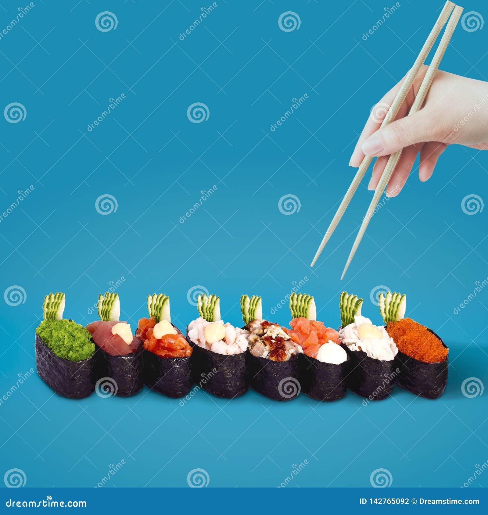 La mano con i bastoncini seleziona i sushi su un fondo blu