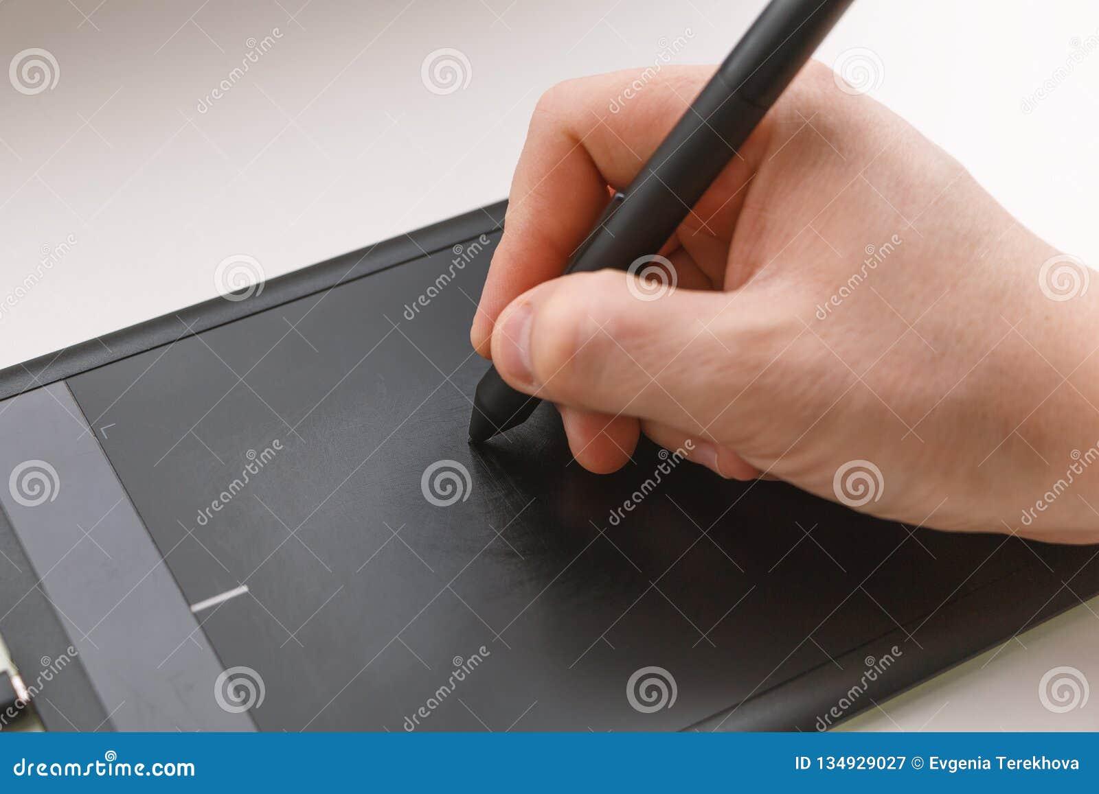 La mano de los hombres dibuja en una tableta de gráficos usando una aguja