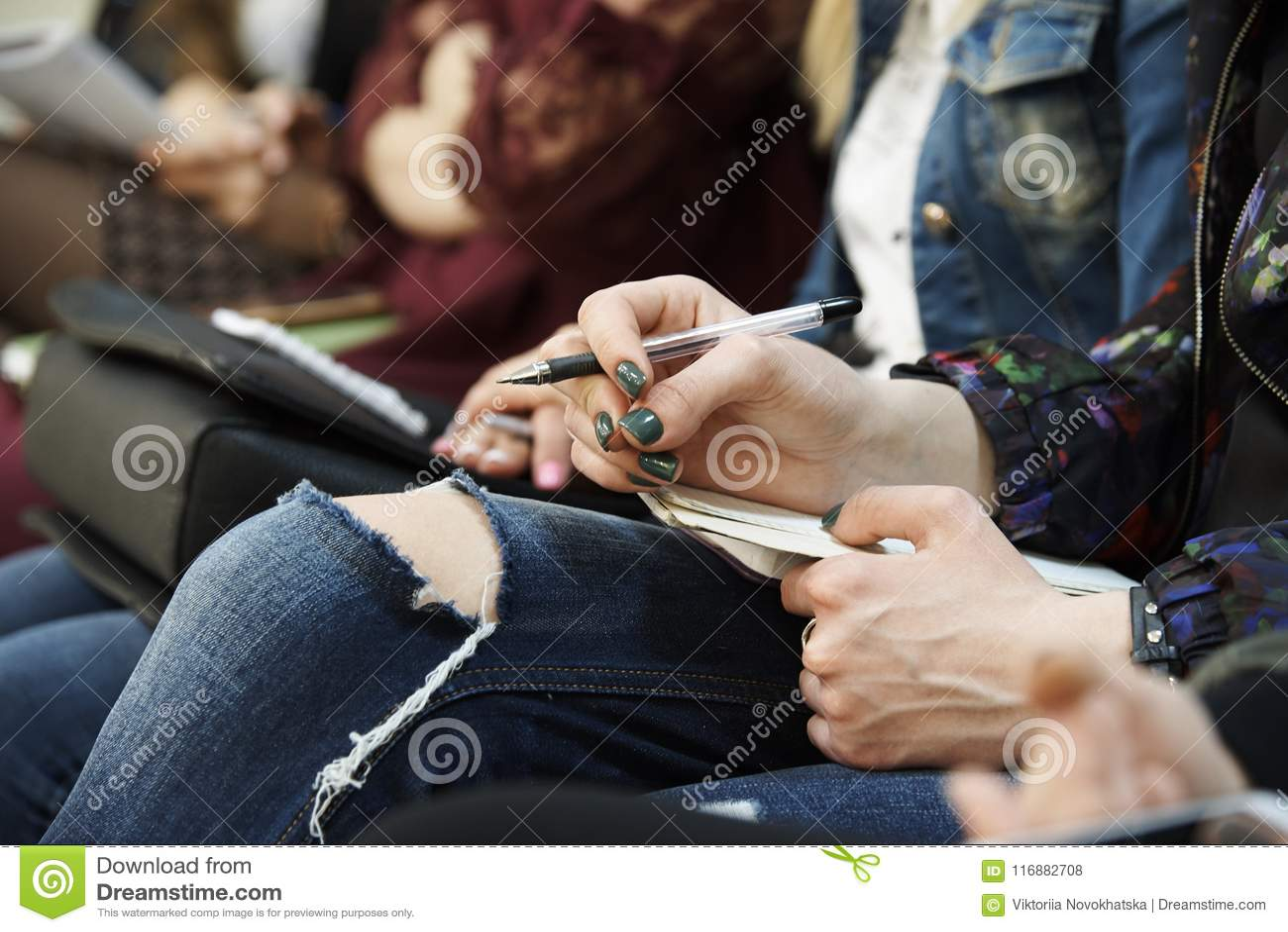 La mano de la muchacha con una pluma y una libreta miente en su primer de las rodillas