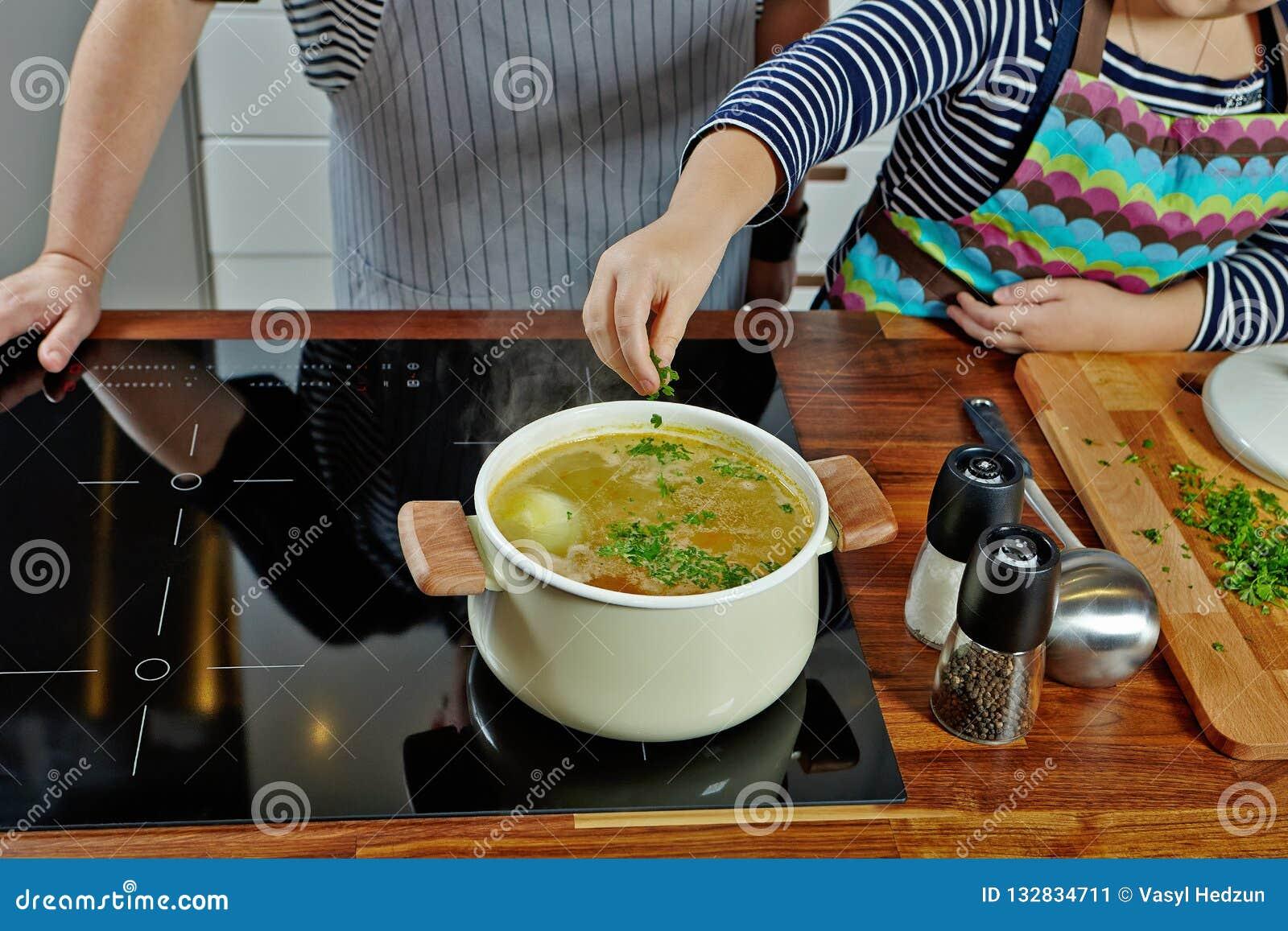 La mano de la muchacha que añade un perejil en la sopa de ebullición Cazo blanco abierto en la estufa negra Cocinar una sopa de f