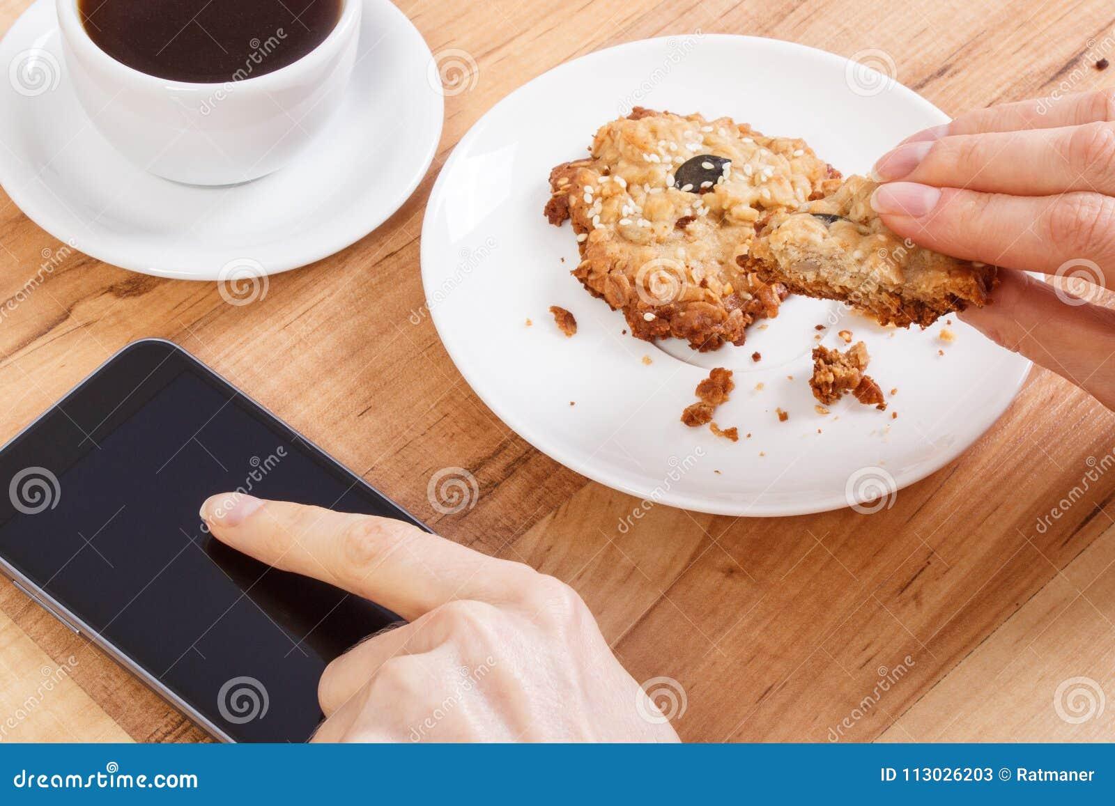 La mano de la mujer que usa el teléfono móvil, las galletas de harina de avena y la taza de café, se relaja con concepto del smar