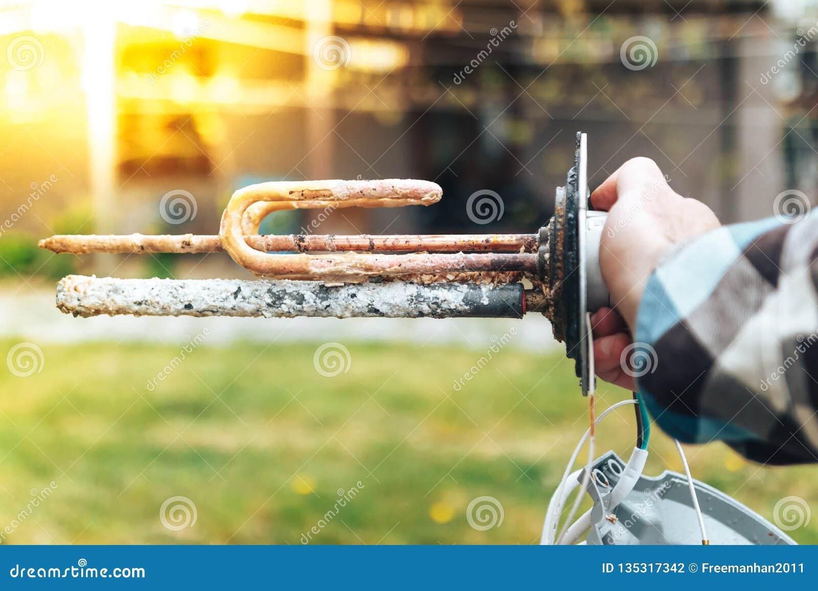 La mano de un hombre blanco, demuestra el efecto destructivo de la escala sobre el elemento de la caldera
