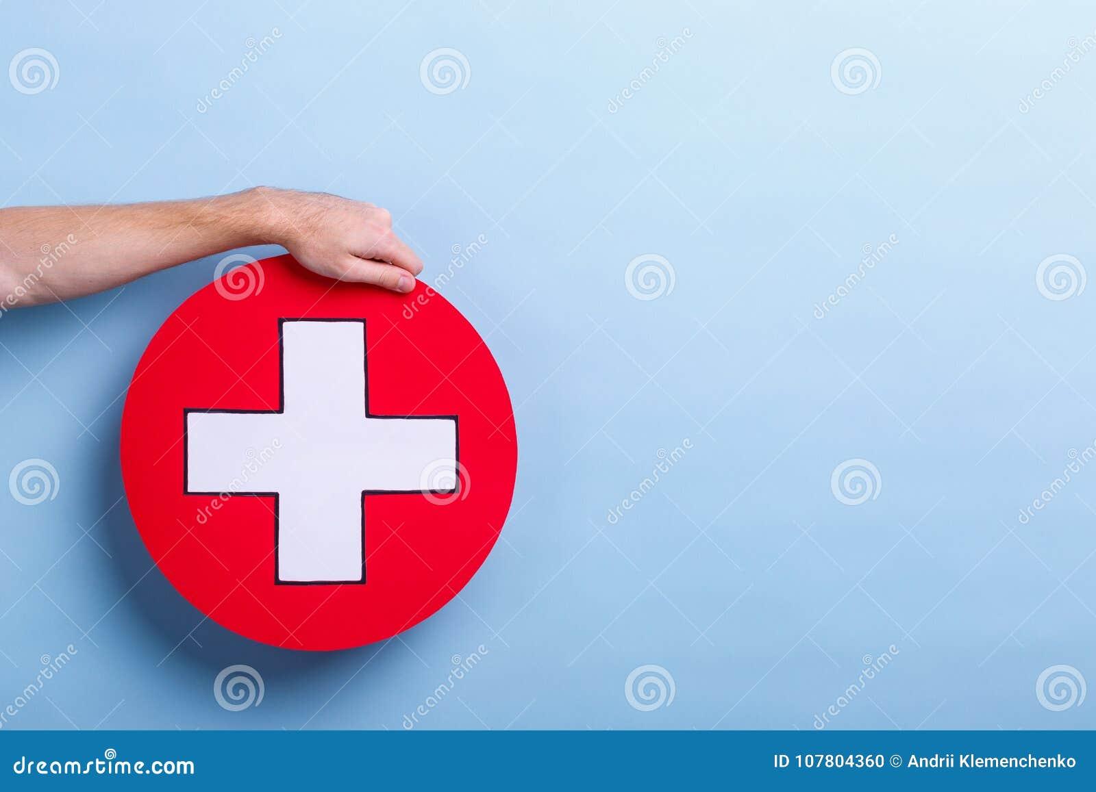 La mano de un hombre lleva a cabo una muestra médica, una cruz en un círculo Fondo azul con un lugar para una inscripción
