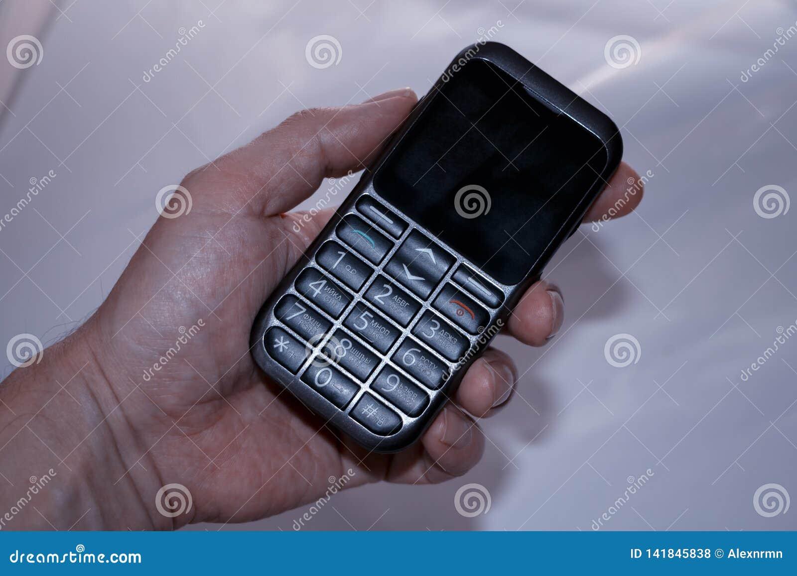 La mano de un hombre sostiene un teléfono de botón viejo