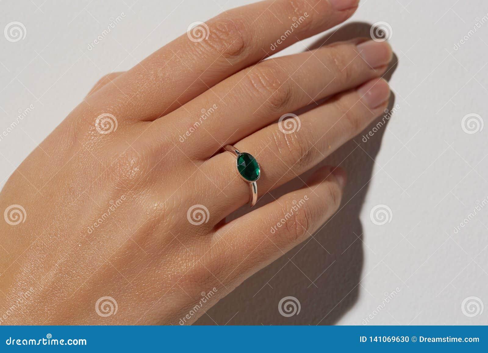 La mano de una mujer con el anillo blanco