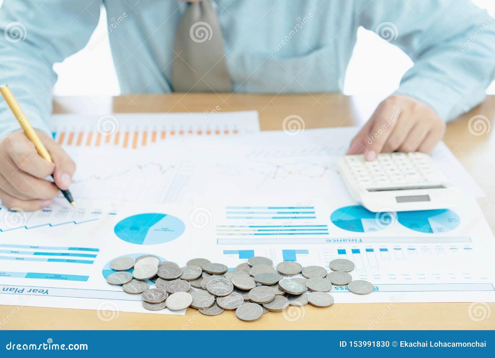 La mano del hombre de negocios usando la calculadora y los informes documentan la fabricación de cuenta financiera