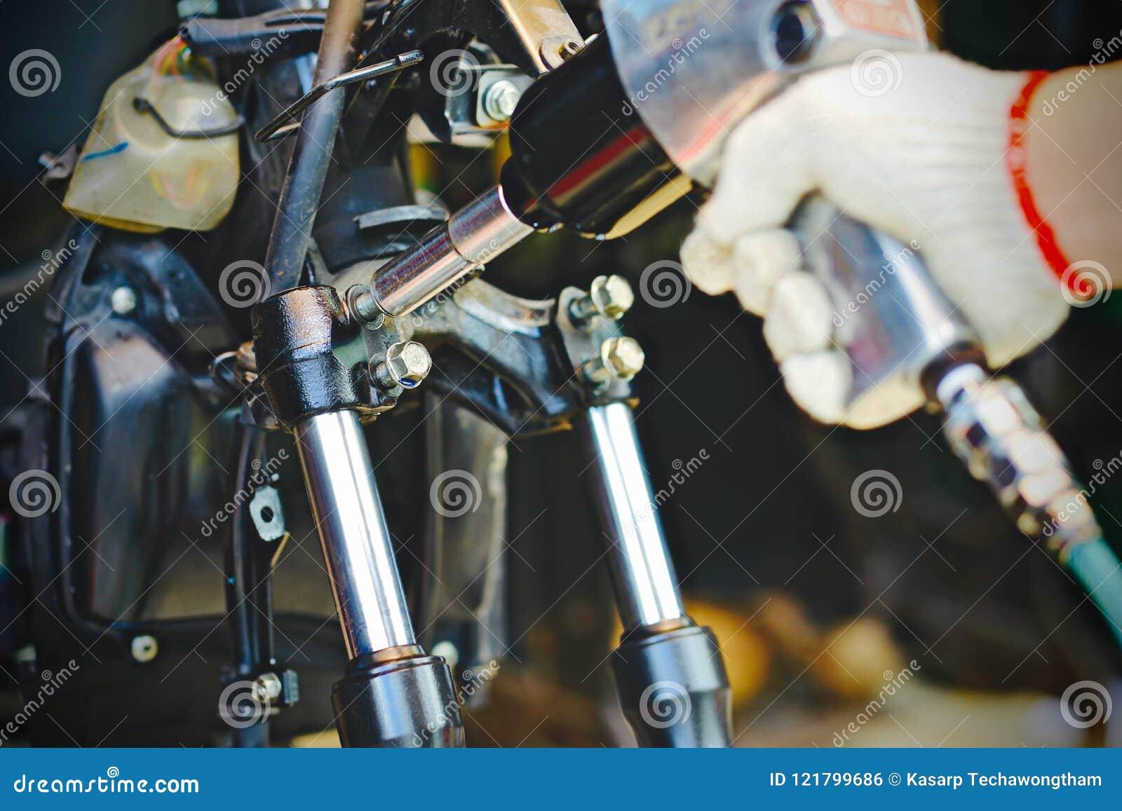 La mano del hombre del mecánico substituye y ajusta el sistema del freno trasero de la motocicleta