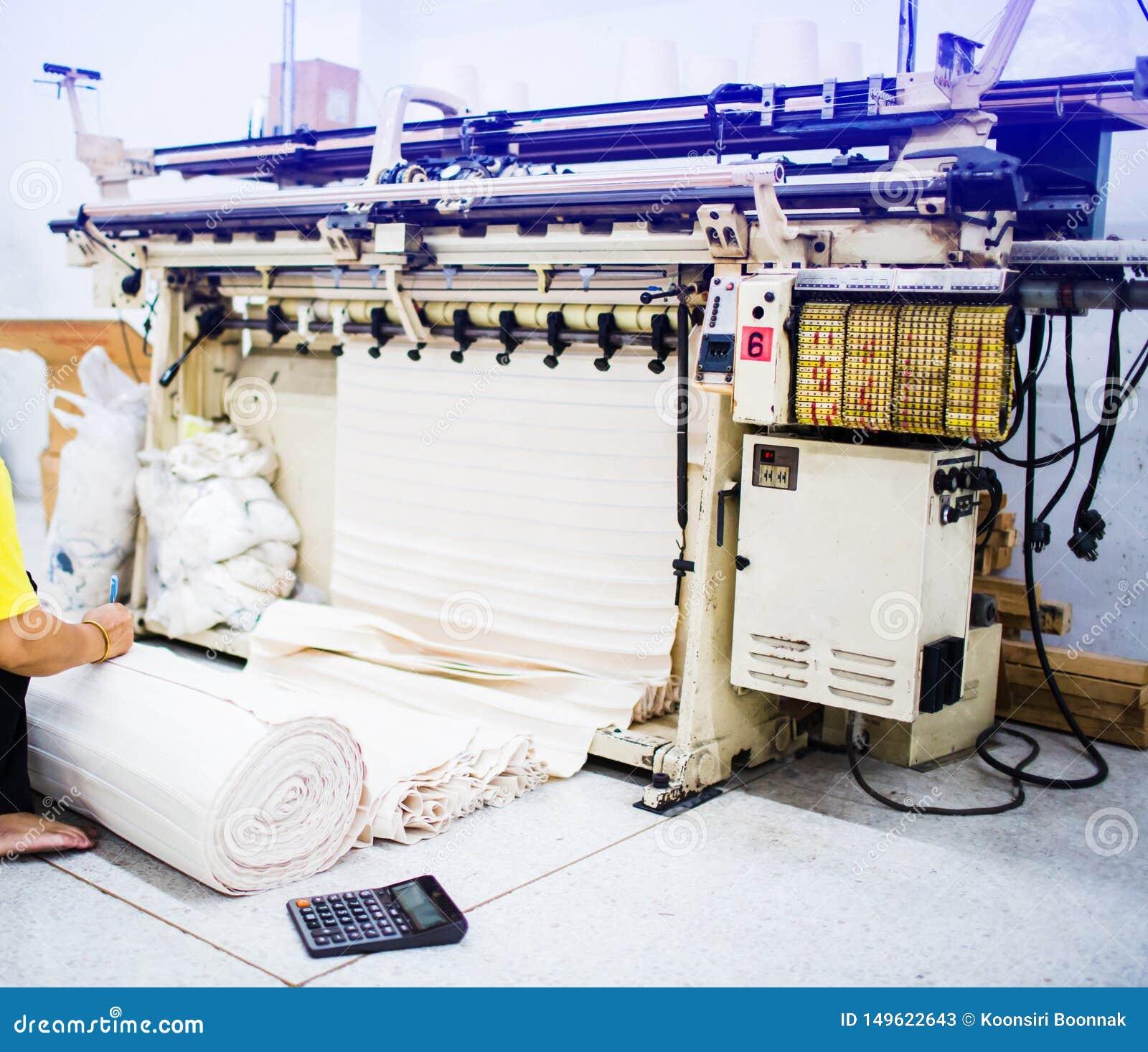 La mano del mecánico está comprobando la tela con una calculadora