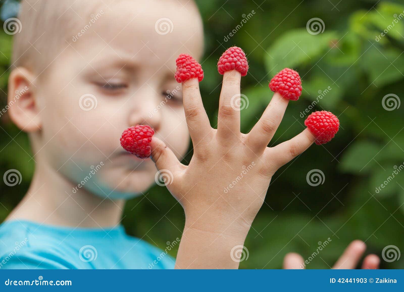 La mano del niño con la frambuesa en los fingeres