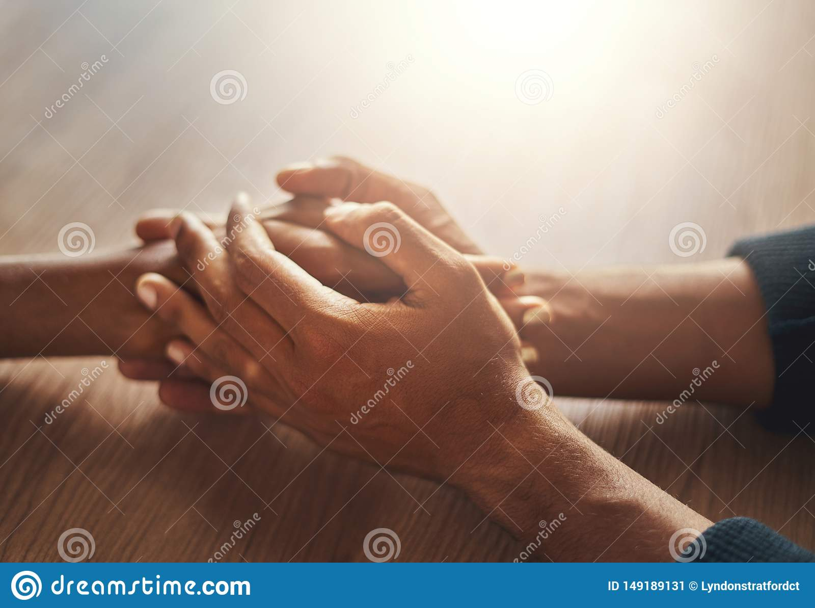 La mano del par que lleva a cabo las manos en el escritorio de madera