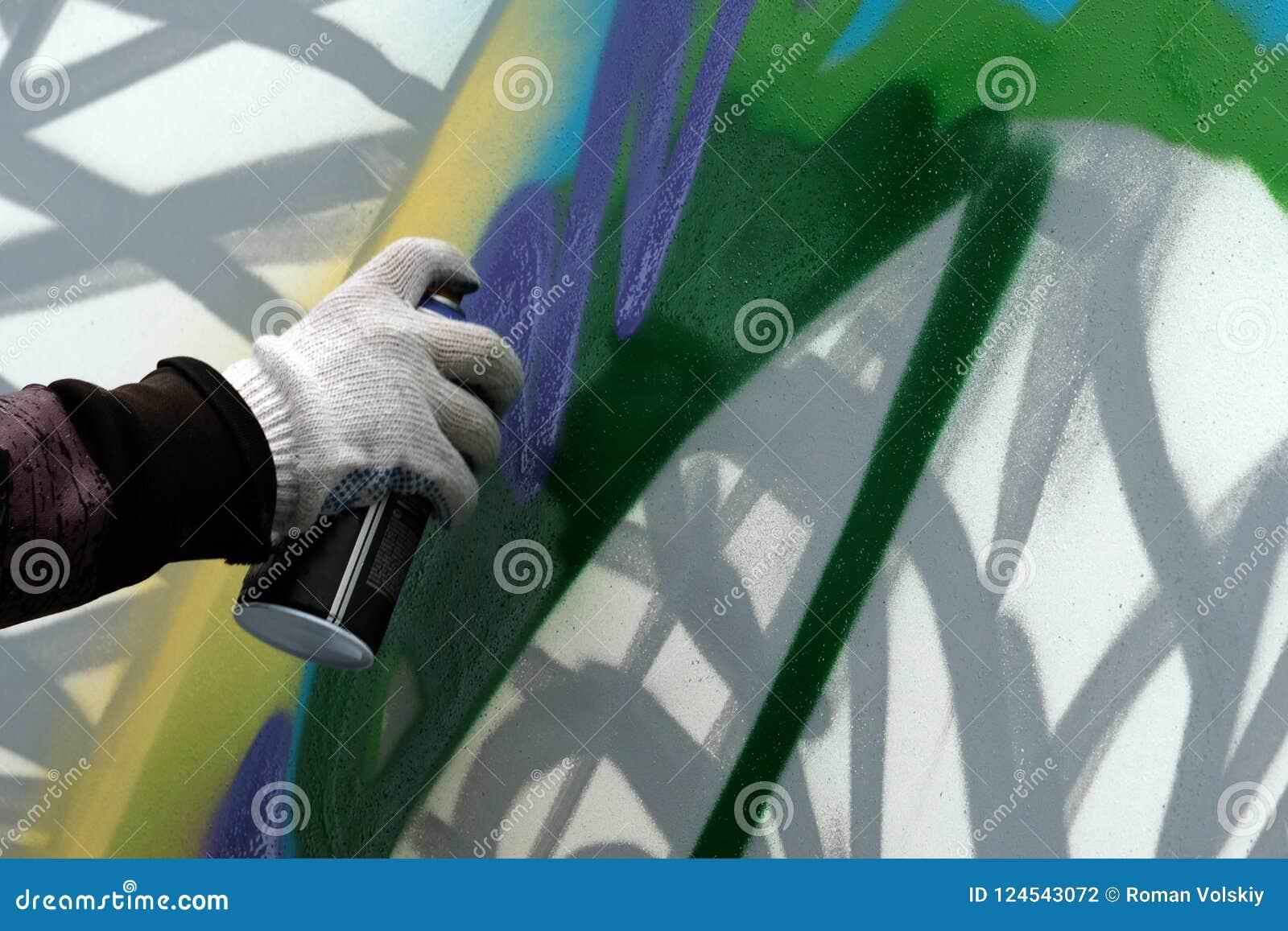 La mano del ` s del artista con un globo de la pintura dibuja la pintada en una pared blanca