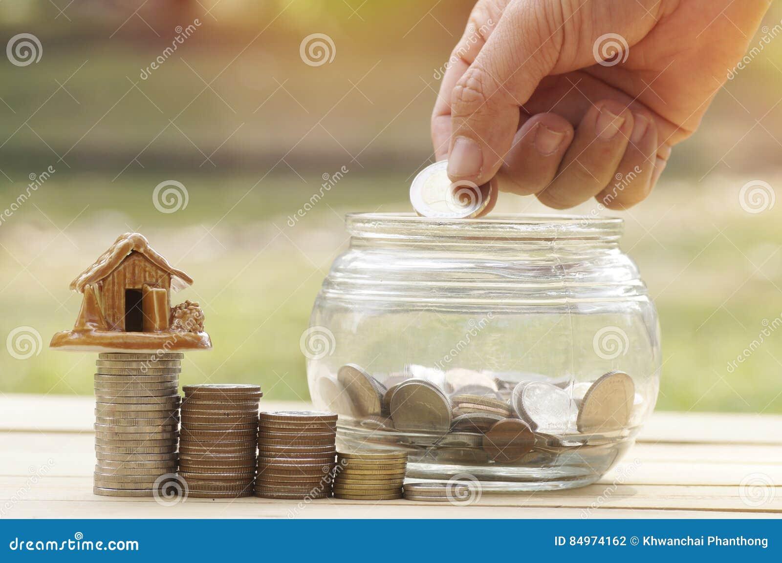 La mano del ` s de las mujeres puso monedas del dinero en la botella de cristal para el concepto de la reserva y de la donación p