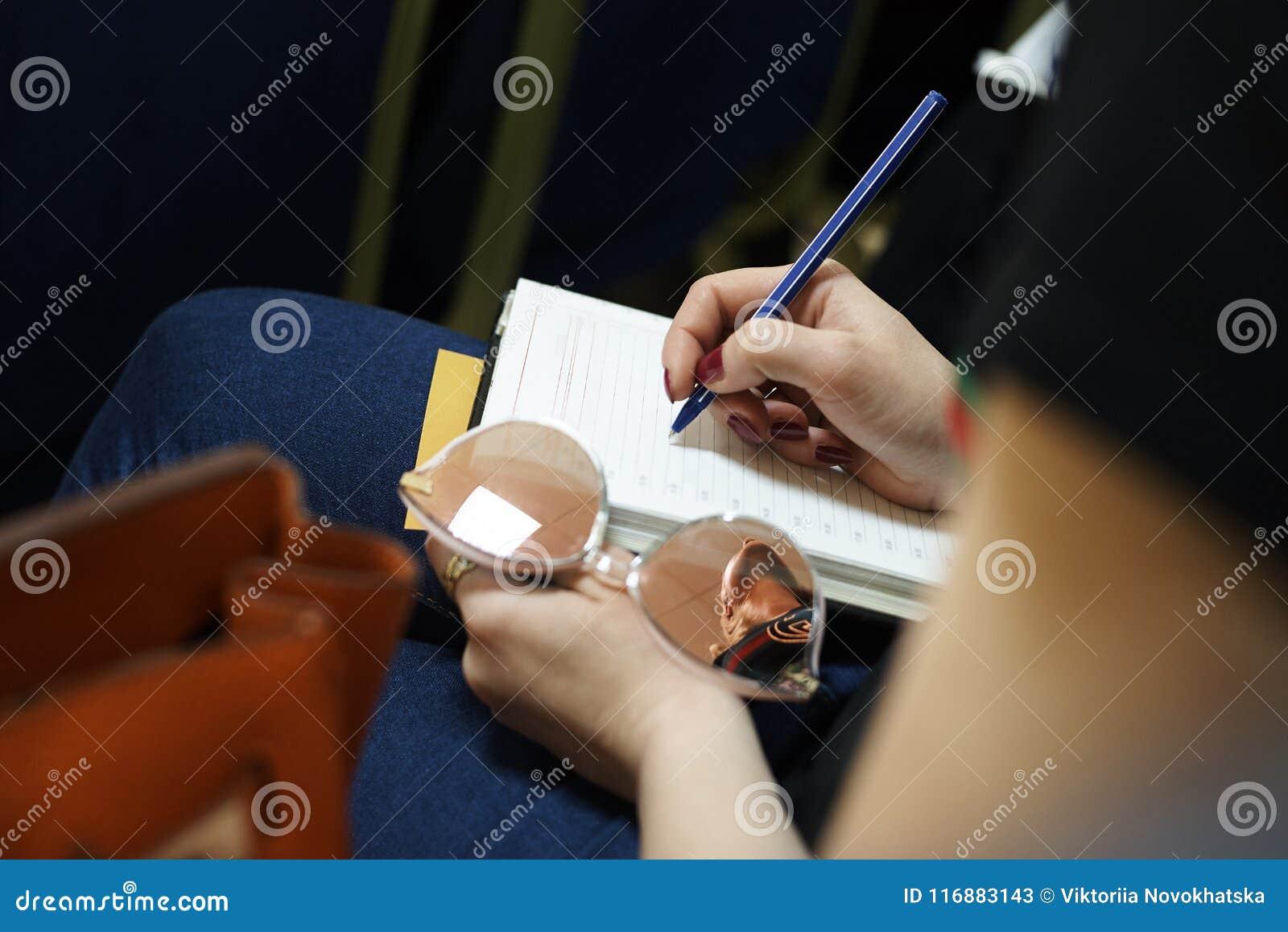 La mano del ` s de la muchacha sostiene una pluma en la hoja de papel