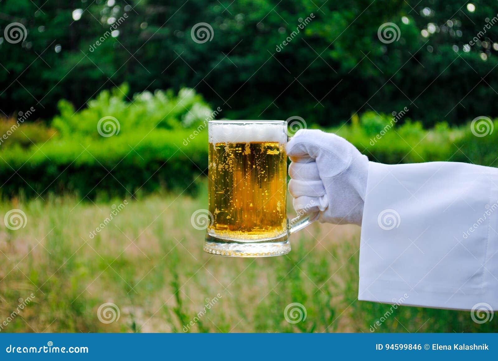 La mano del ` s del camarero en un guante del blanco sostiene un vidrio de cerveza contra la perspectiva de la naturaleza