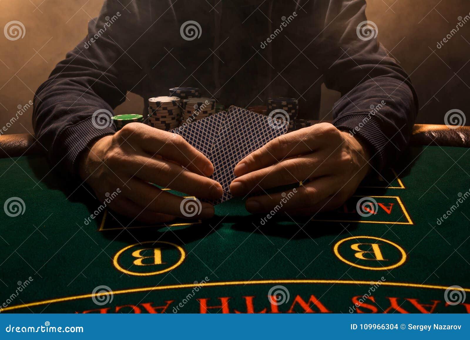 La mano del ` s del hombre con los naipes se cierra para arriba Microprocesadores del juego de tarjeta del casino Ponga los naipe