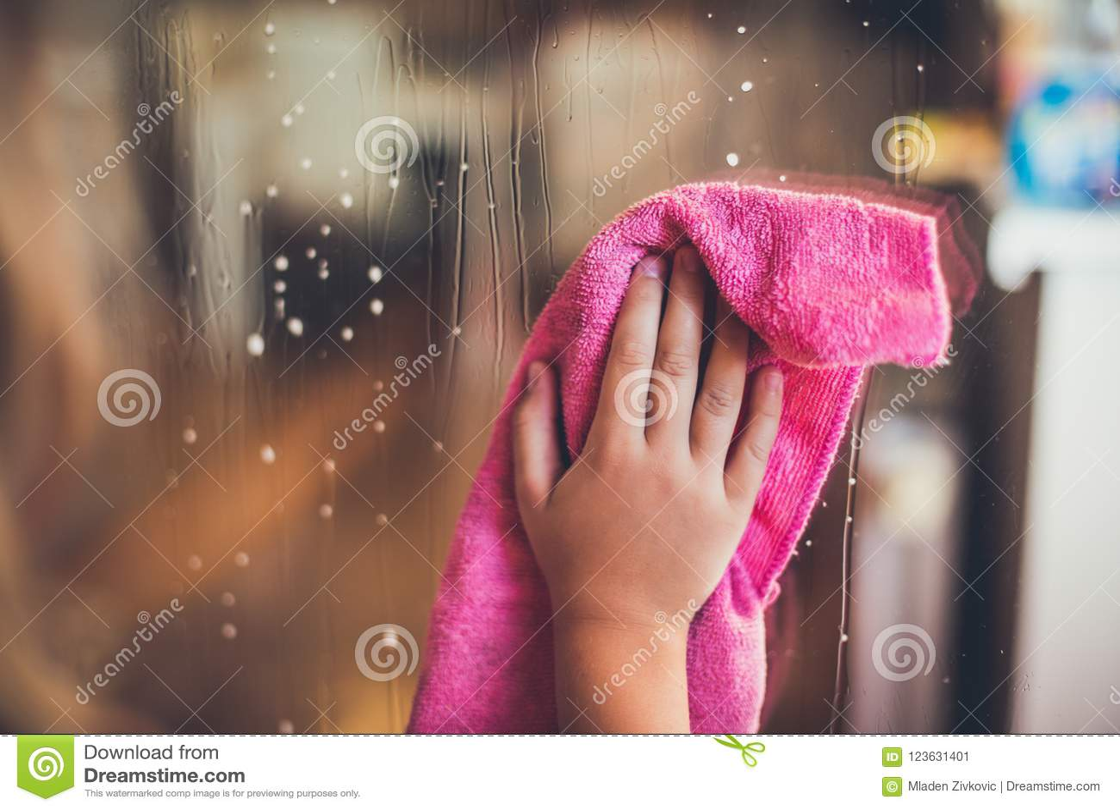 La mano del ` s del niño limpia la ventana