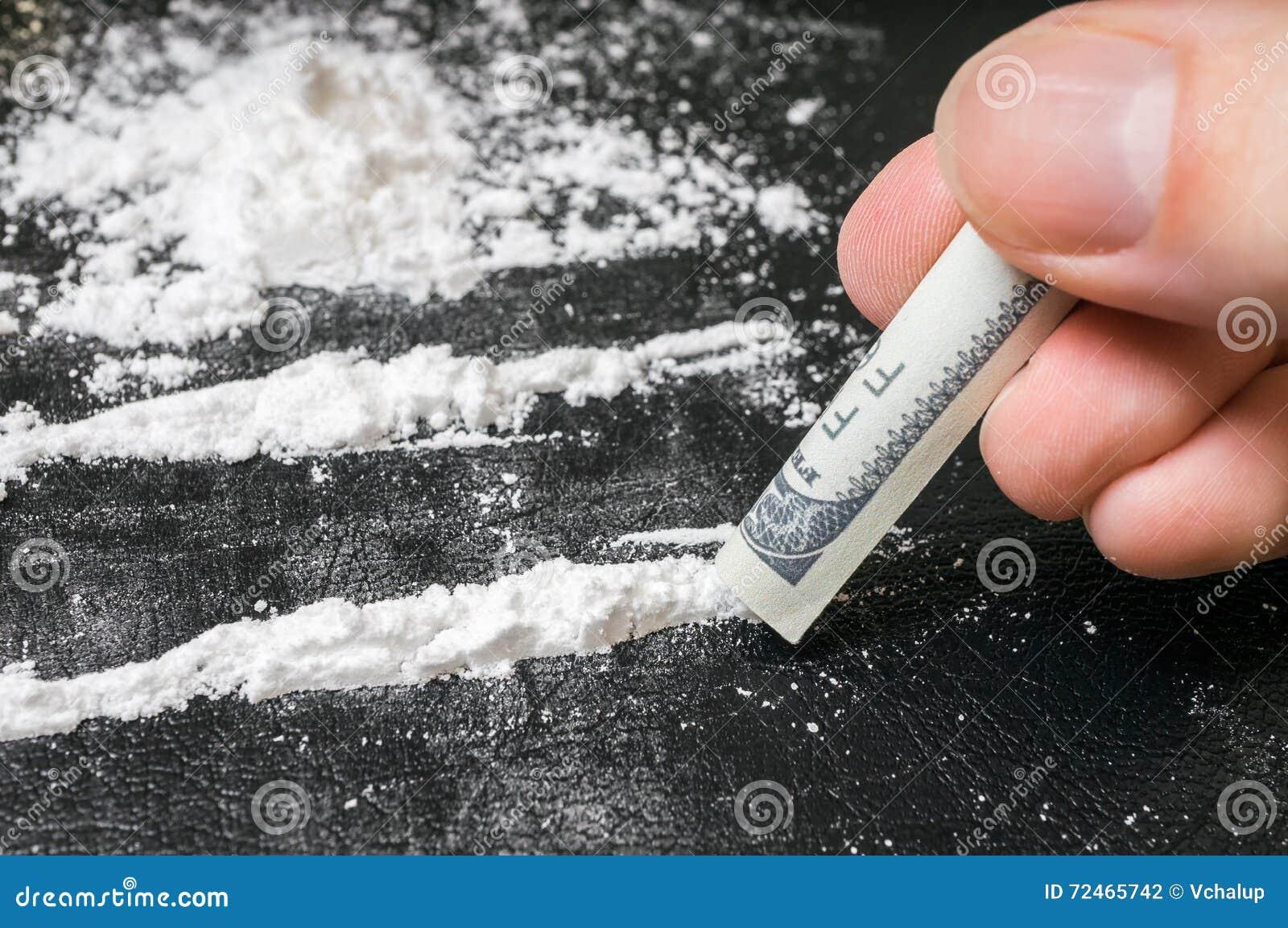 La mano dell uomo tiene la banconota rotolata per sniffare la polvere della cocaina