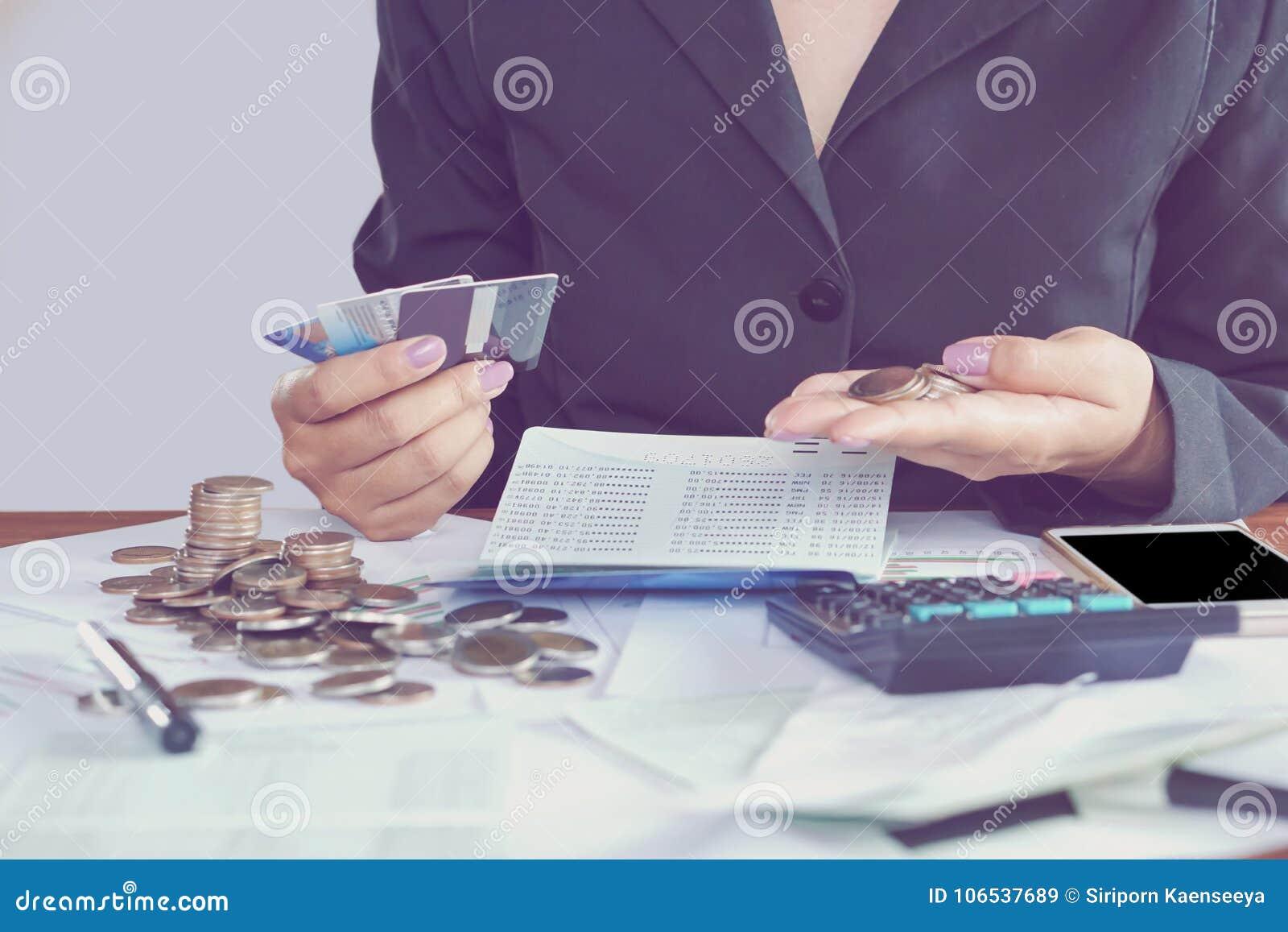 La mano della donna di affari che calcolano le sue spese mensili durante la stagione di imposta con le monete, il calcolatore, la