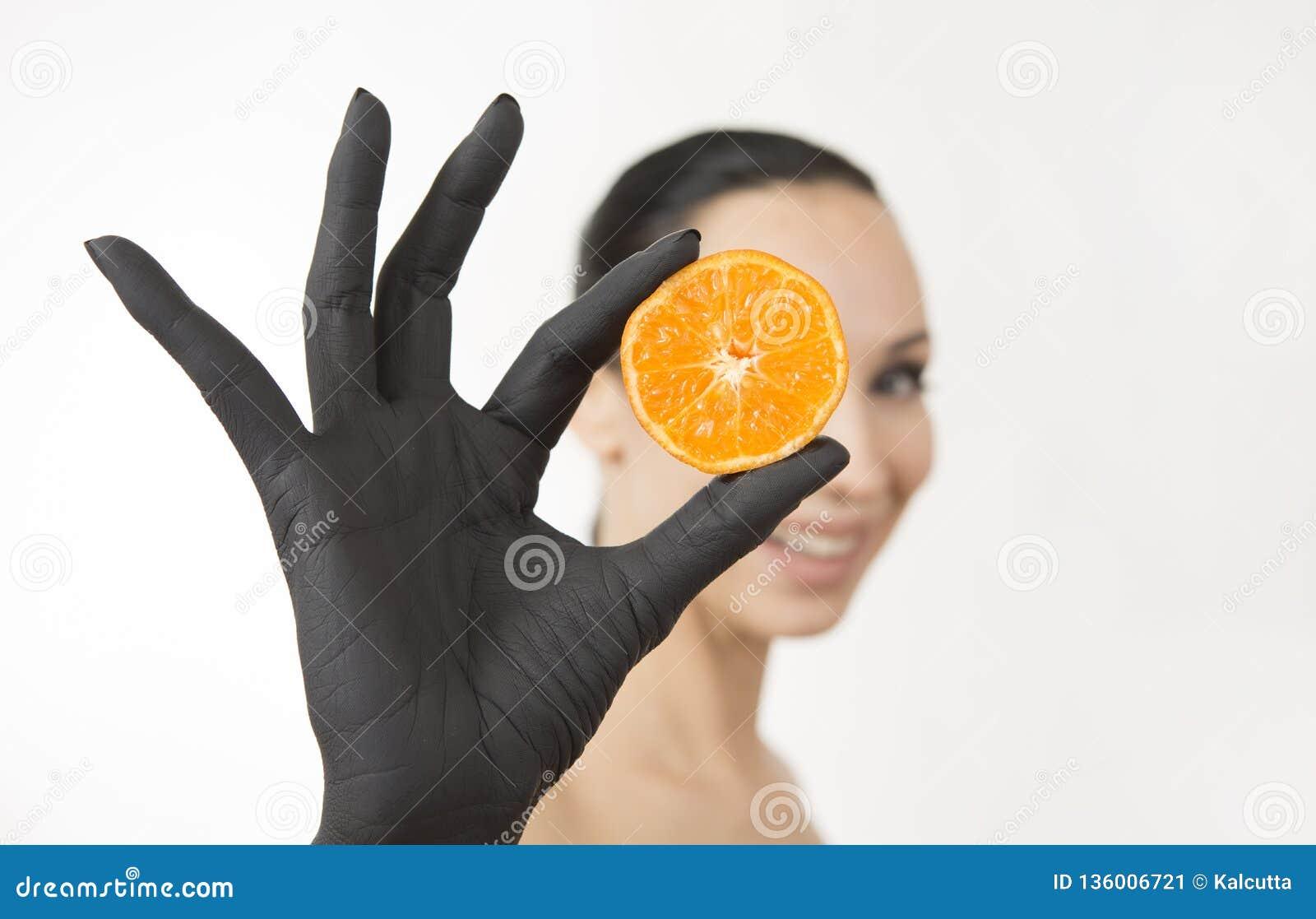 La mano della donna di colore che tiene le metà arancio vicino al suo fronte Mano nera con il mandarino saporito luminoso