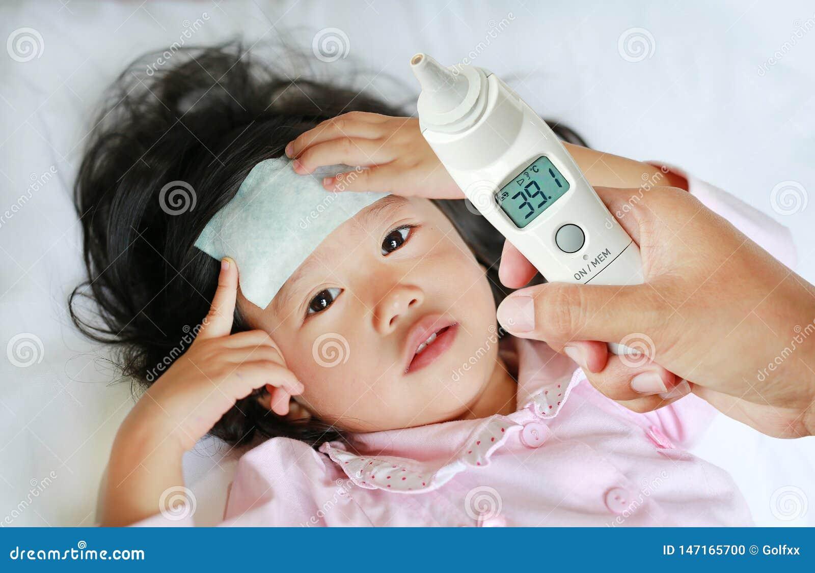 La mano della madre del primo piano prende la temperatura per sua figlia con il termometro di orecchio sul letto a casa
