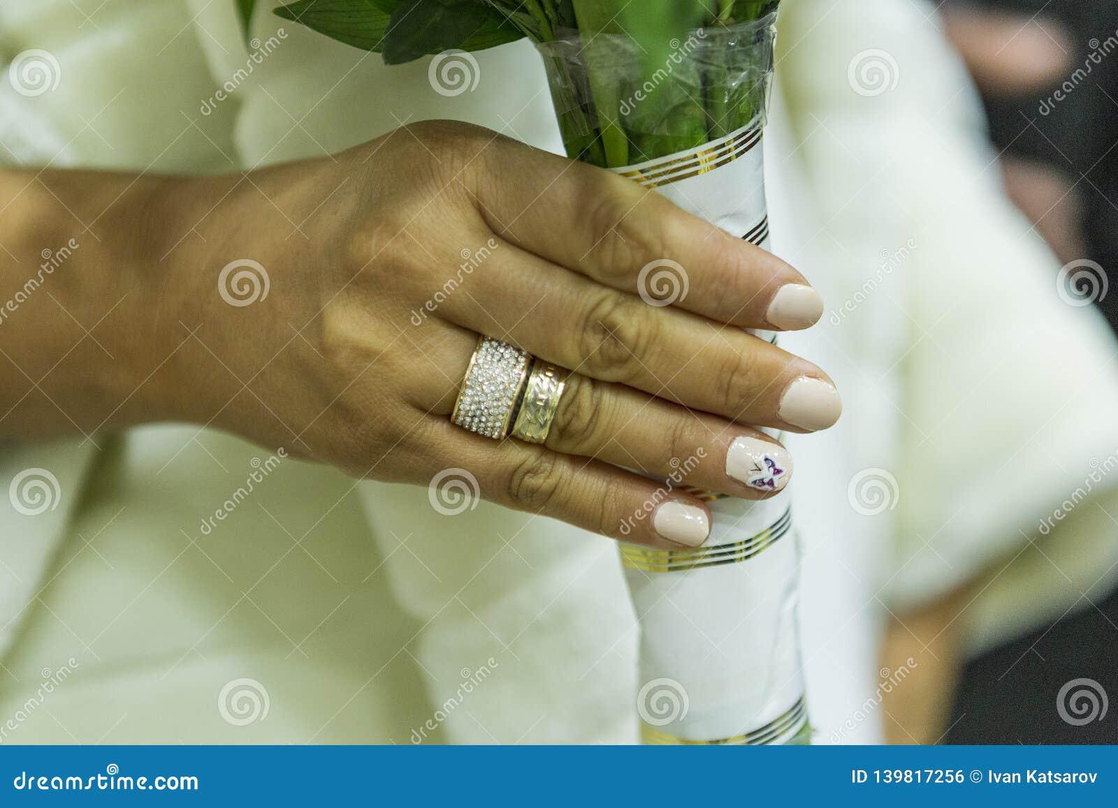 La mano della sposa con l anello di fidanzamento e la fede nuziale tiene un mazzo dei fiori