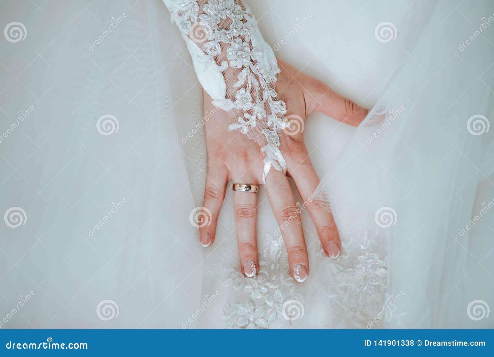 La mano della sposa sul suo vestito da sposa con l anello