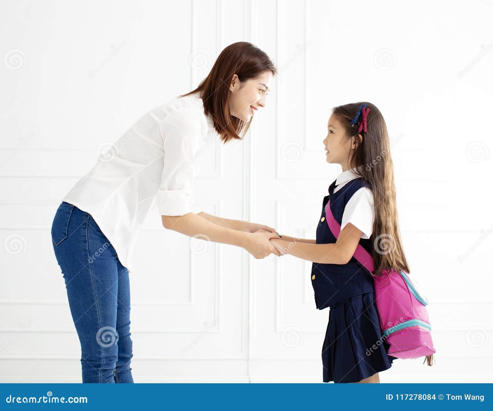 La mano della tenuta della madre della figlia pronta va a scuola