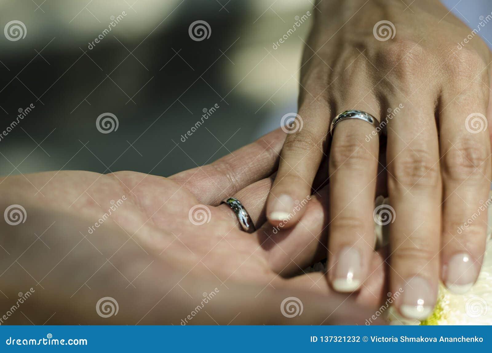 La mano dello sposo e della sposa che tiene insieme con le fedi nuziali