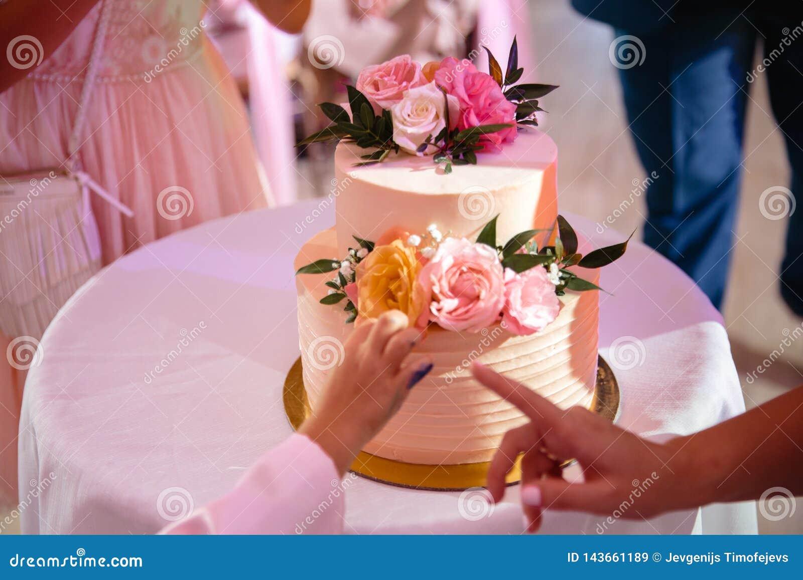 La mano di un bambino che pende verso la torta nunziale nello stile naturale ecologico - il suo genitore indica con il suo dito c