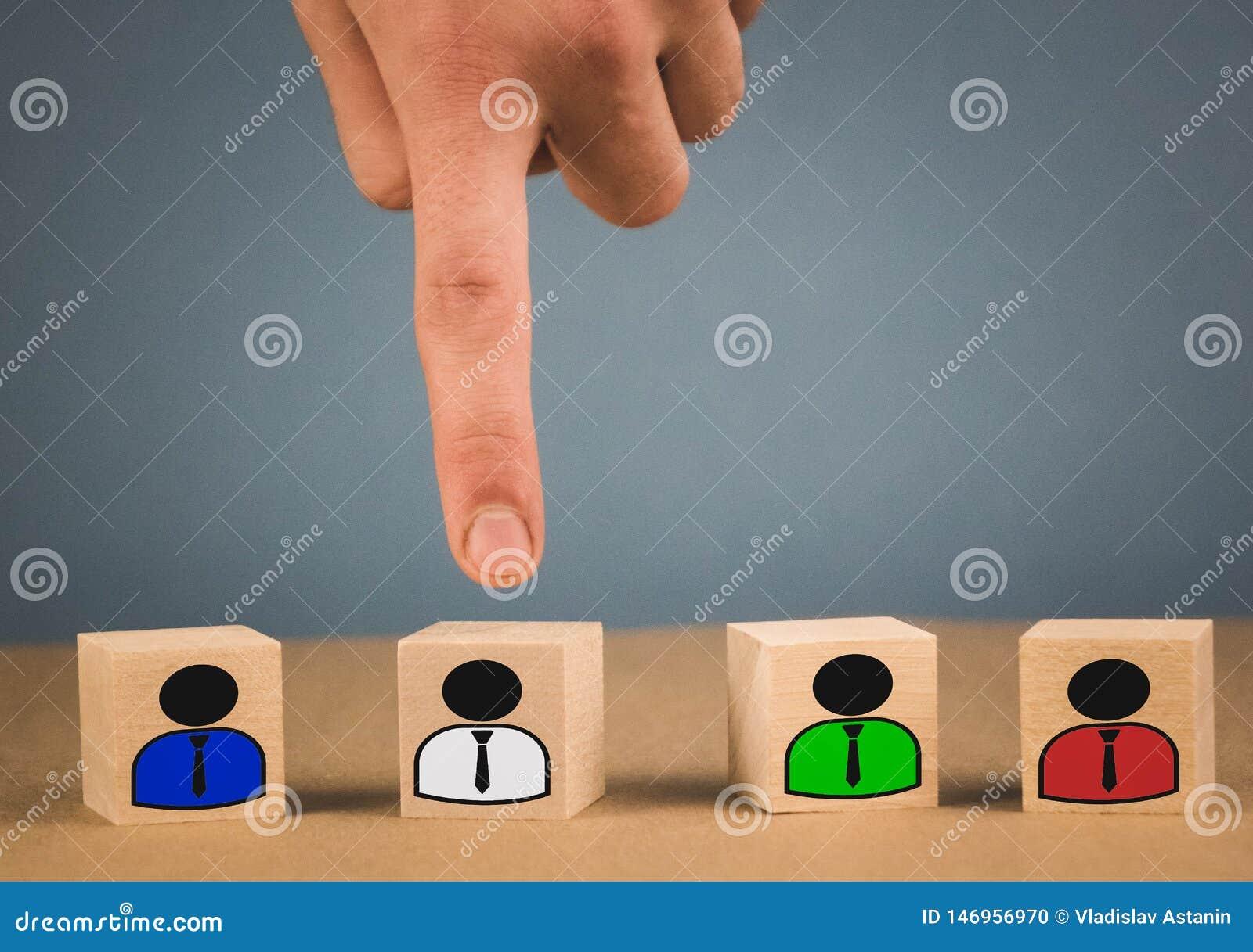 La mano escoge un cubo de madera con un hombre en una camisa blanca