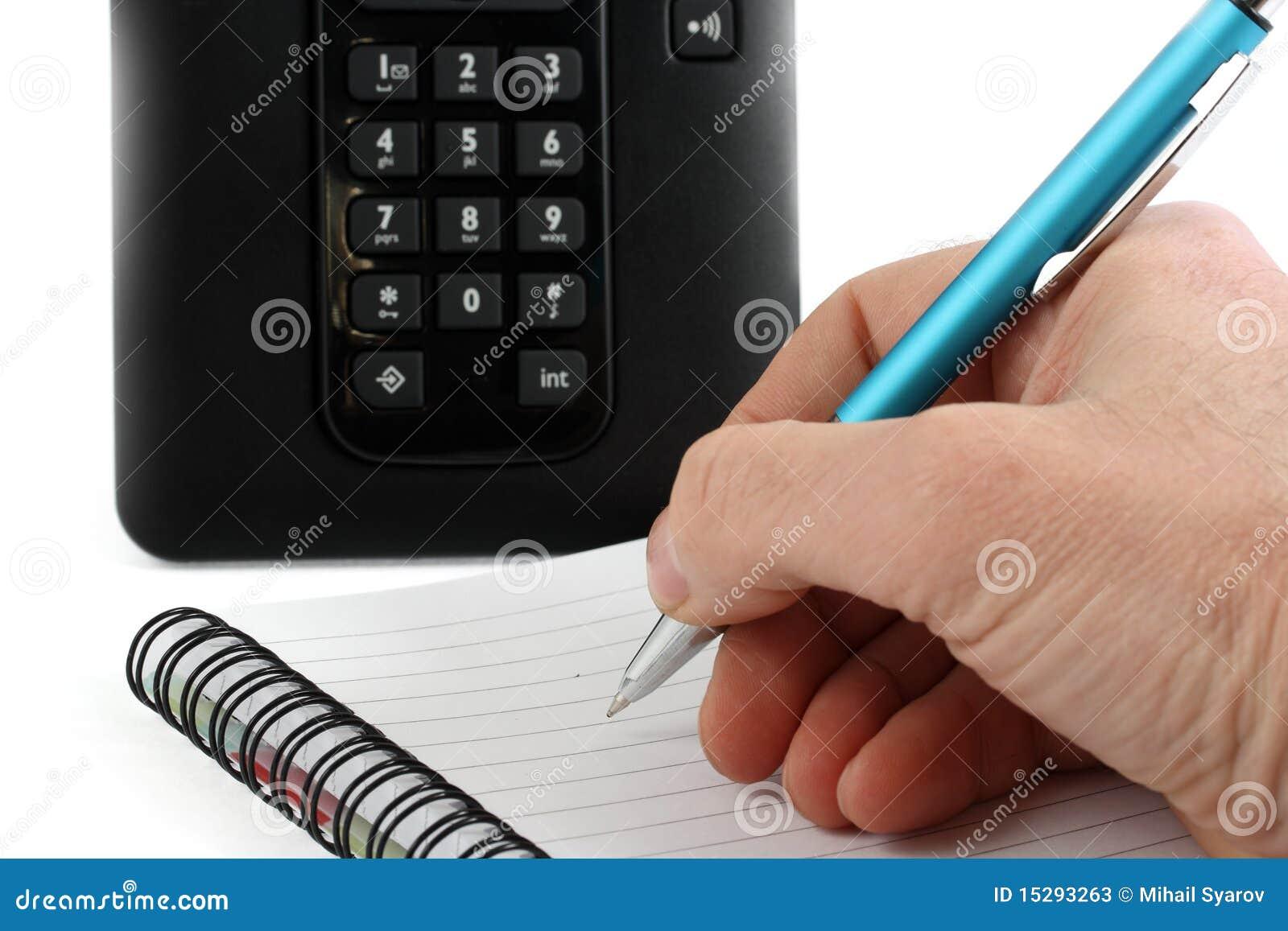 La mano escribe una pluma en un cuaderno