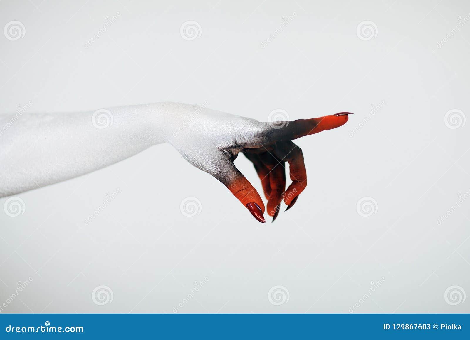 La mano espeluznante de la bruja del monstruo de Halloween con blanco, rojo y el negro componen y de largo las uñas y spiderweb e