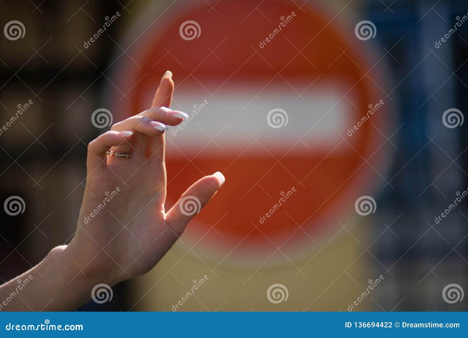 La mano femenina en no incorpora el fondo de la señal de tráfico