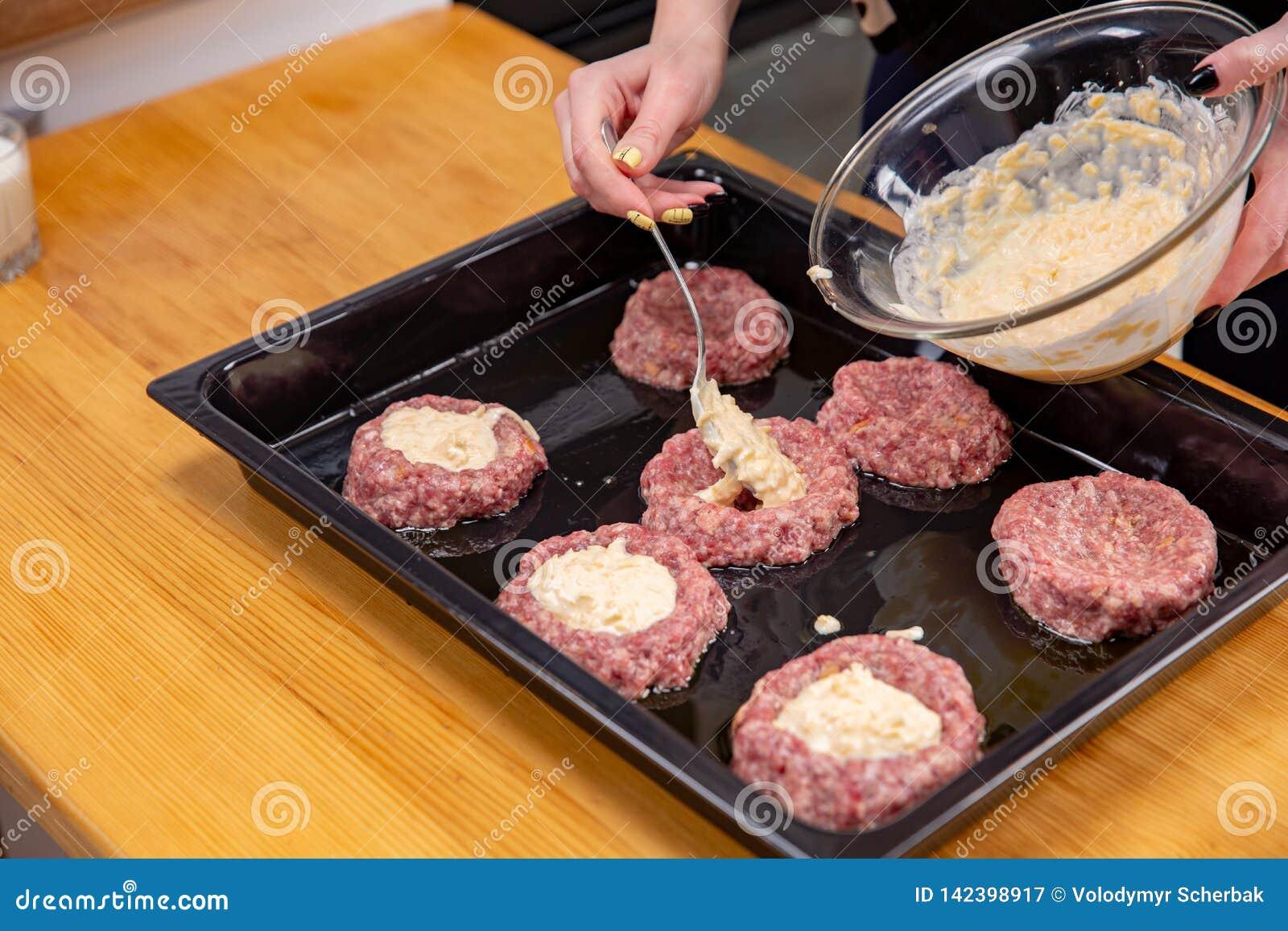 La mano femenina sobrepone el relleno de la carne o de las albóndigas theminced que ponen en una bandeja que cuece negra Proceso