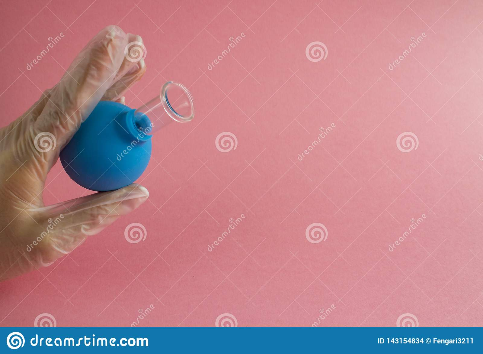 La mano femminile con il manicure francese nel guanto della medicina tiene il barattolo medico cosmetico blu per il massaggio fac
