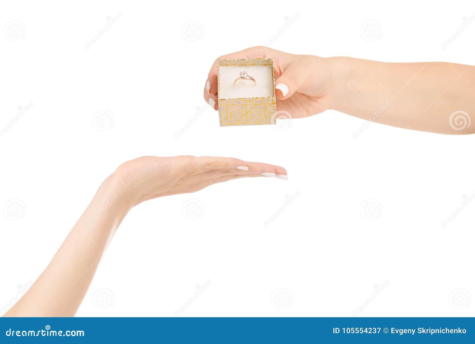 La mano femminile dà una scatola con un anello di oro