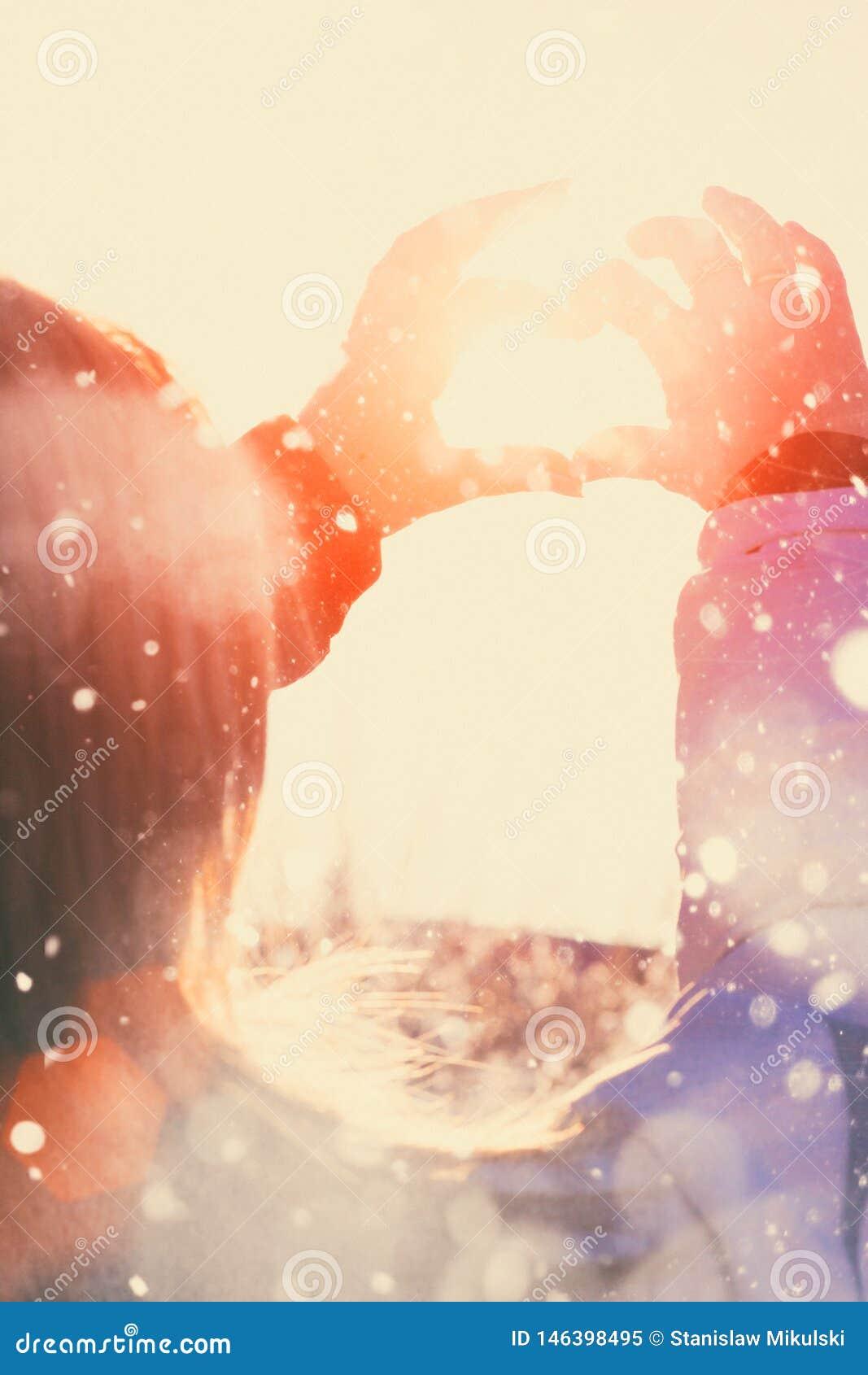 La mano ha modellato il cuore contro il fondo del cielo