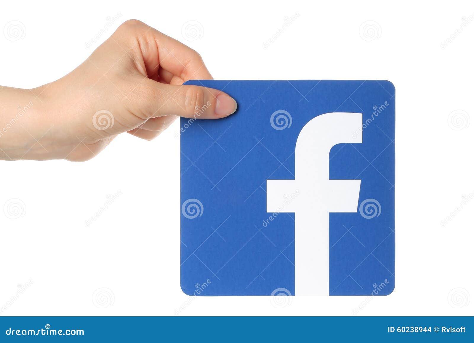 La mano lleva a cabo el logotipo del facebook
