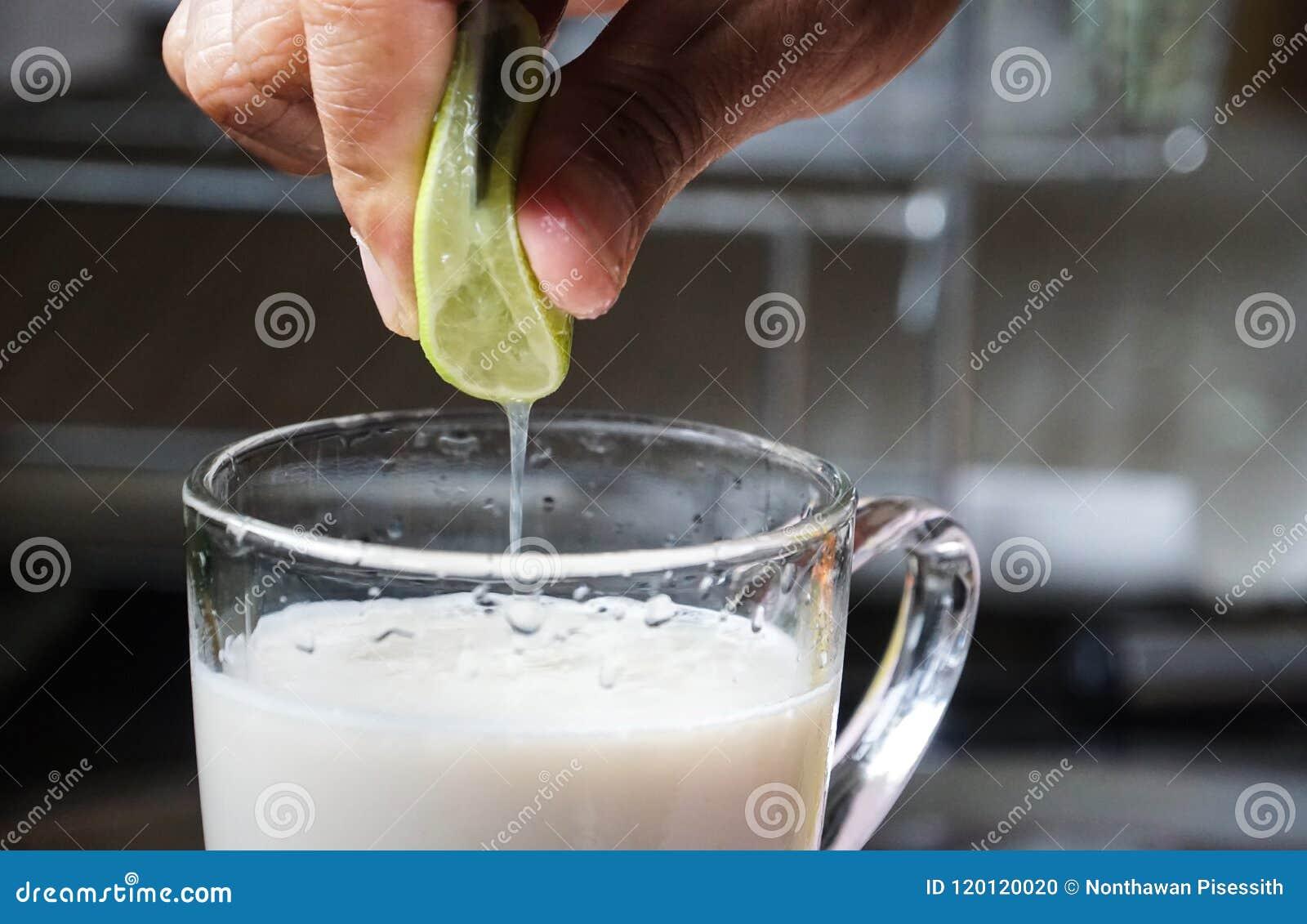 La mano maschio ha messo la calce in bevanda del latte di soia