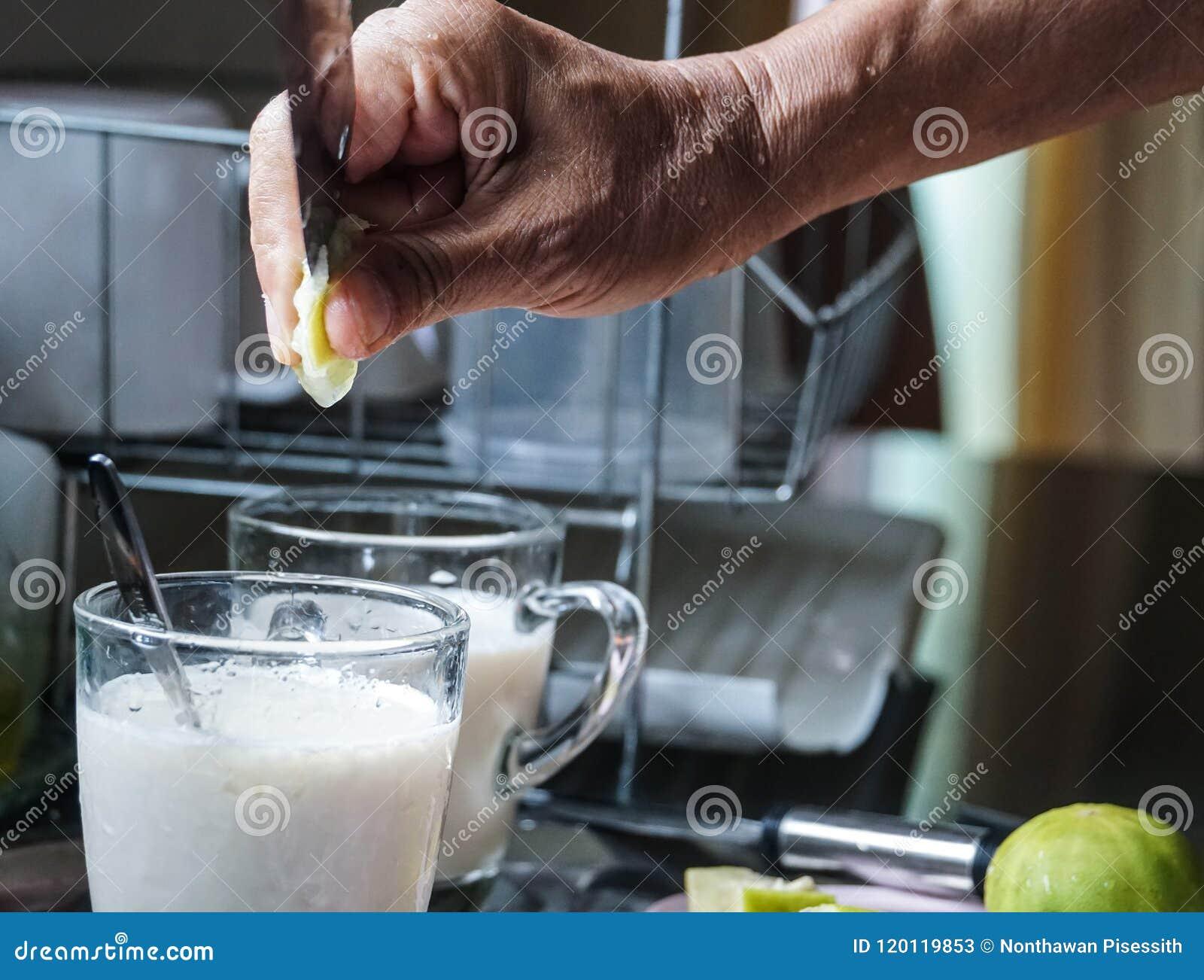 La mano masculina puso la cal en bebida de la leche de soja