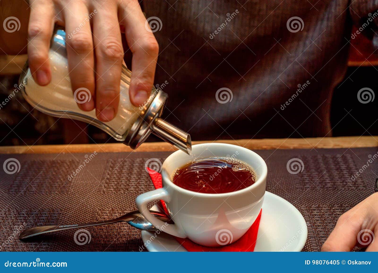 La mano mette lo zucchero in tazza con tè