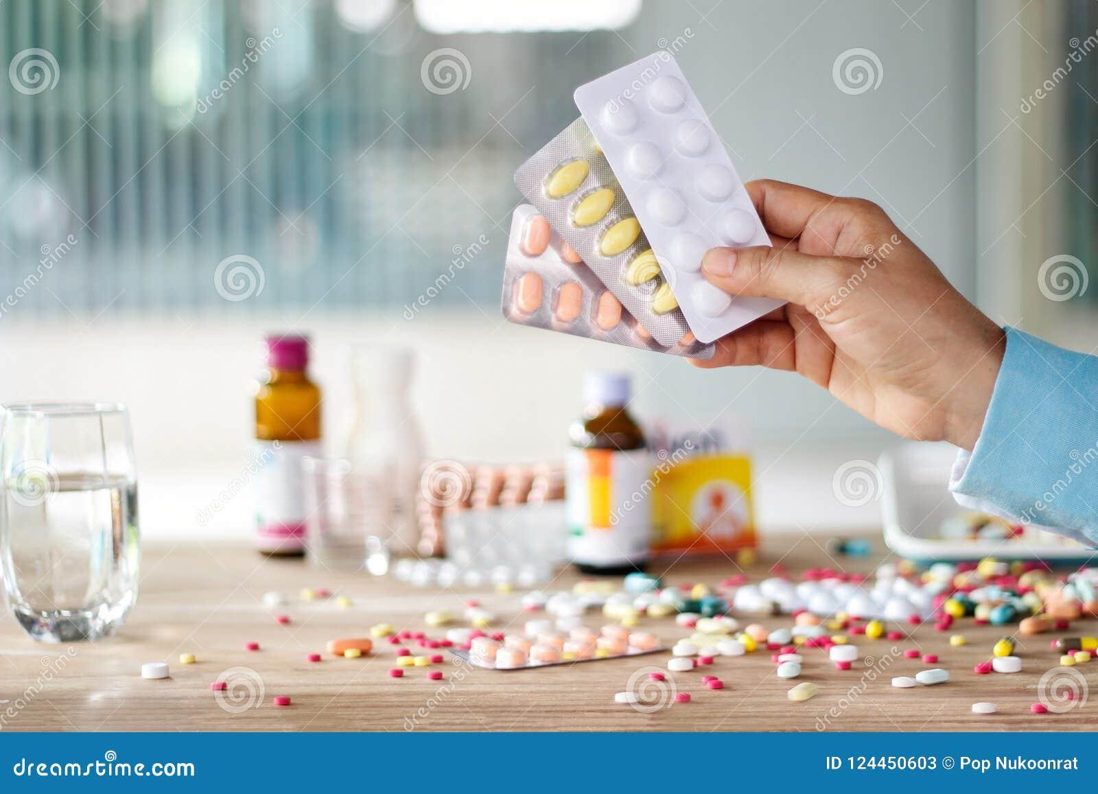 La mano que llevaba a cabo el paquete de la píldora de las medicinas con las drogas coloridas se separó encendido