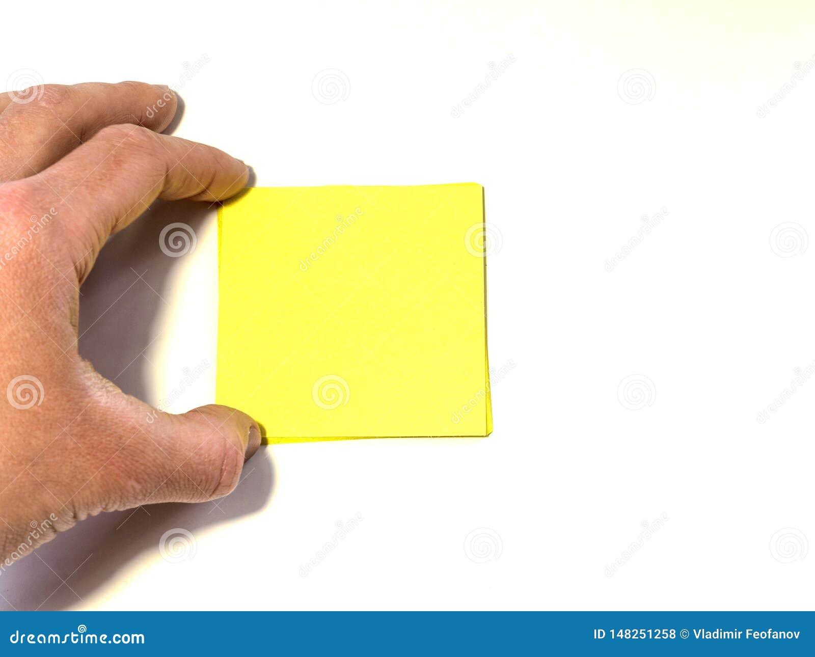 La mano tiene o allunga ad un foglio giallo di carta a forma di quadrato in